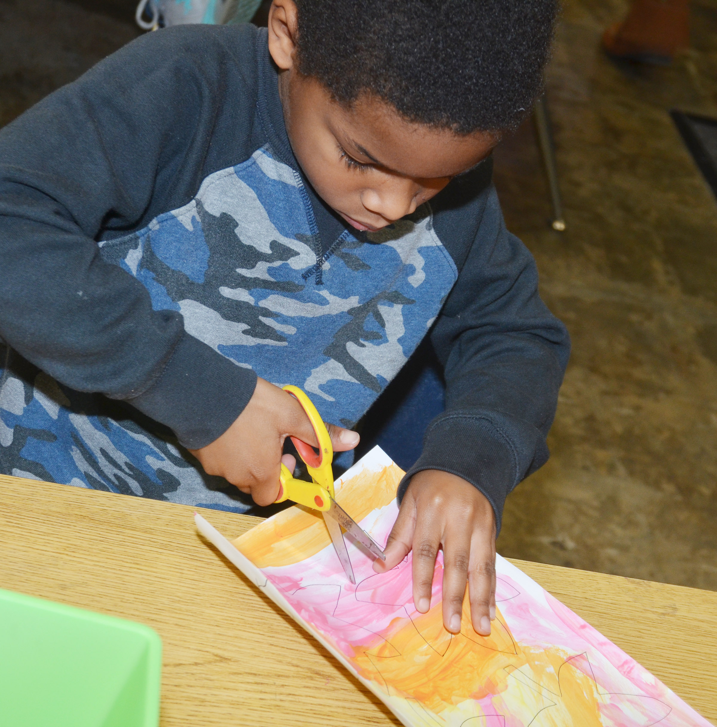 CES kindergartener Kaiyden Vancleave cuts out his leaves.
