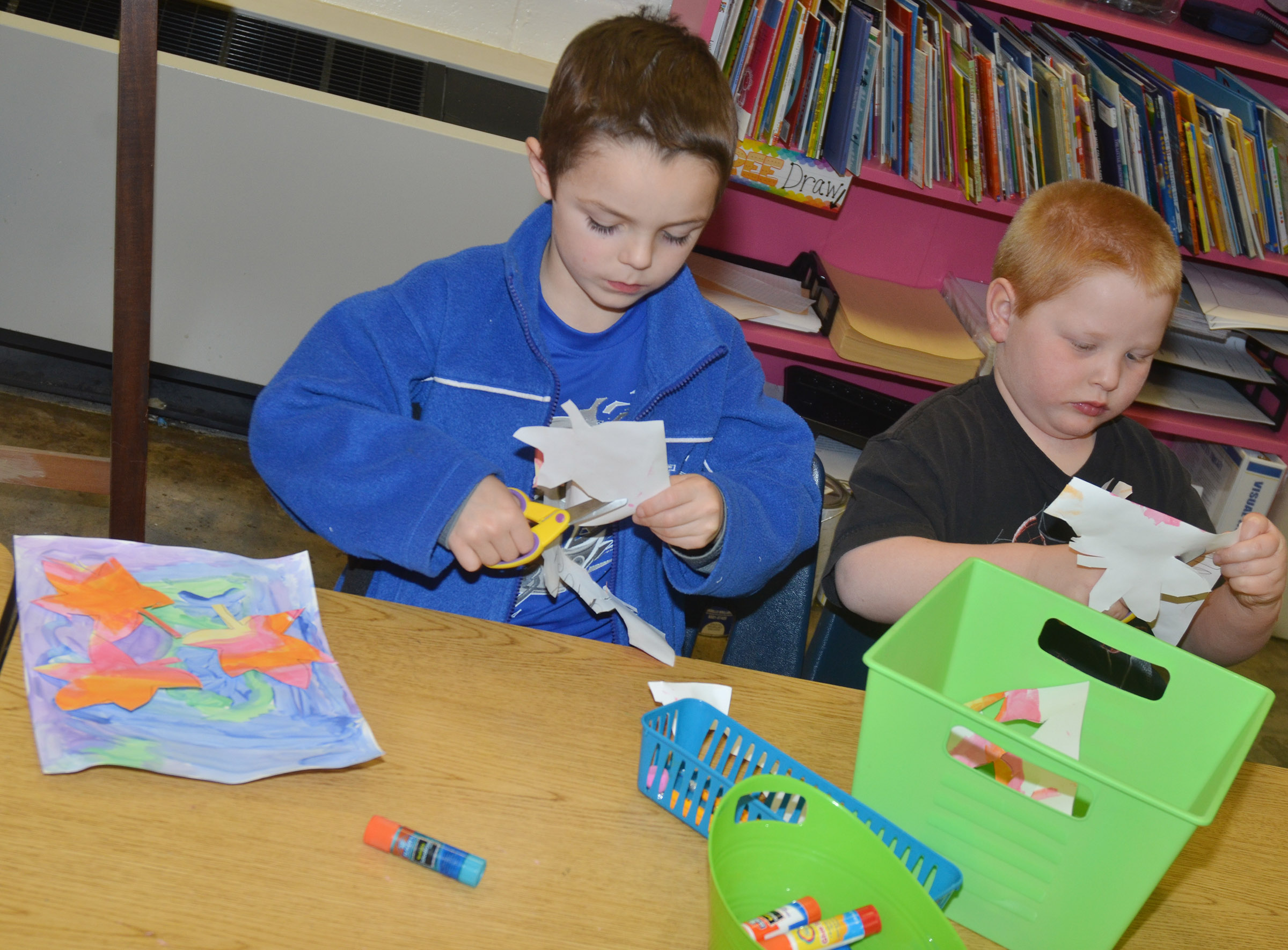 CES kindergarteners Hayden Goff, at left, and Konnar Hicks cut out their leaves to glue on their cool color paintings.