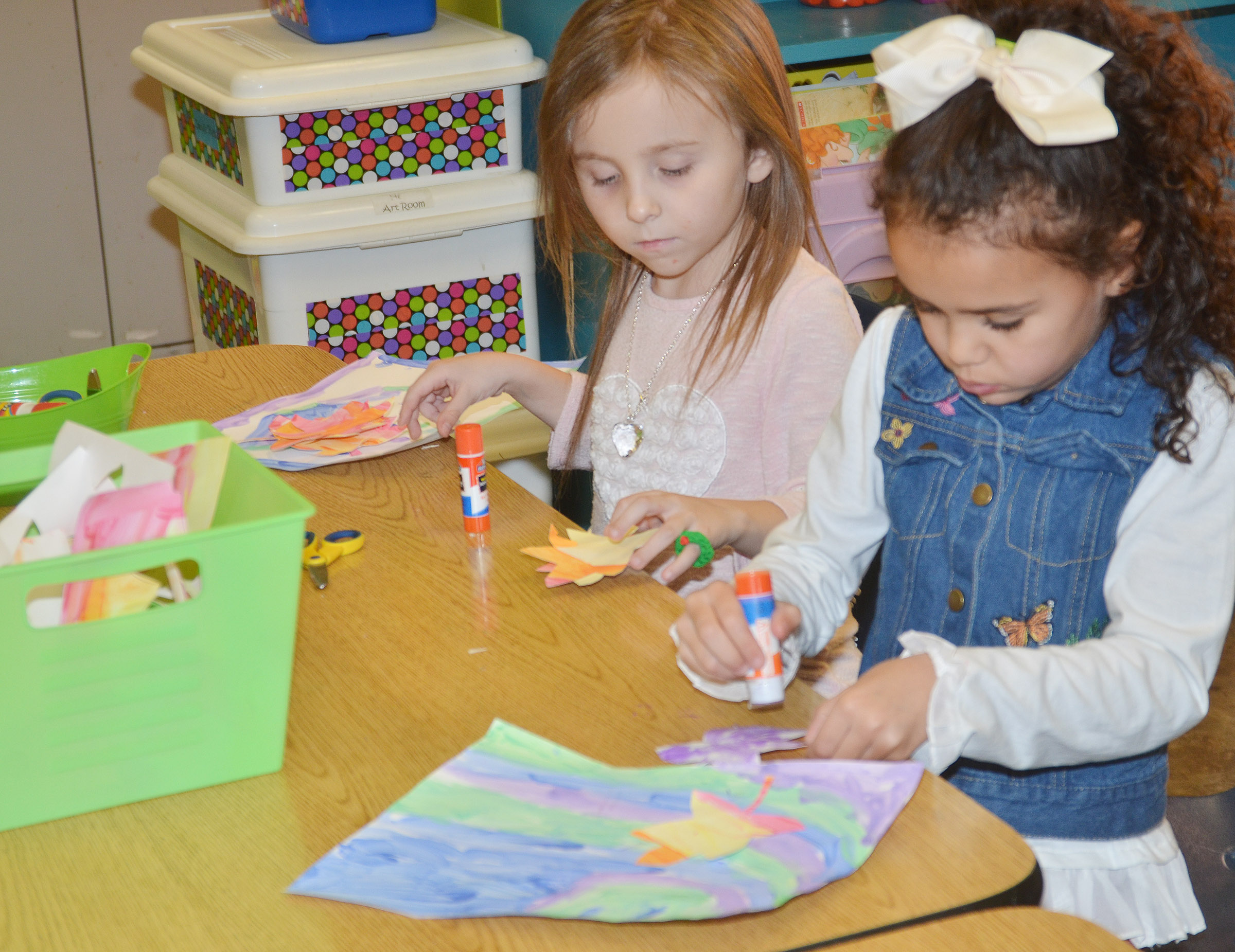 CES kindergarteners Tabitha Leggett, at left, and Adelyn Litsey glue their leaves on their cool color paintings.