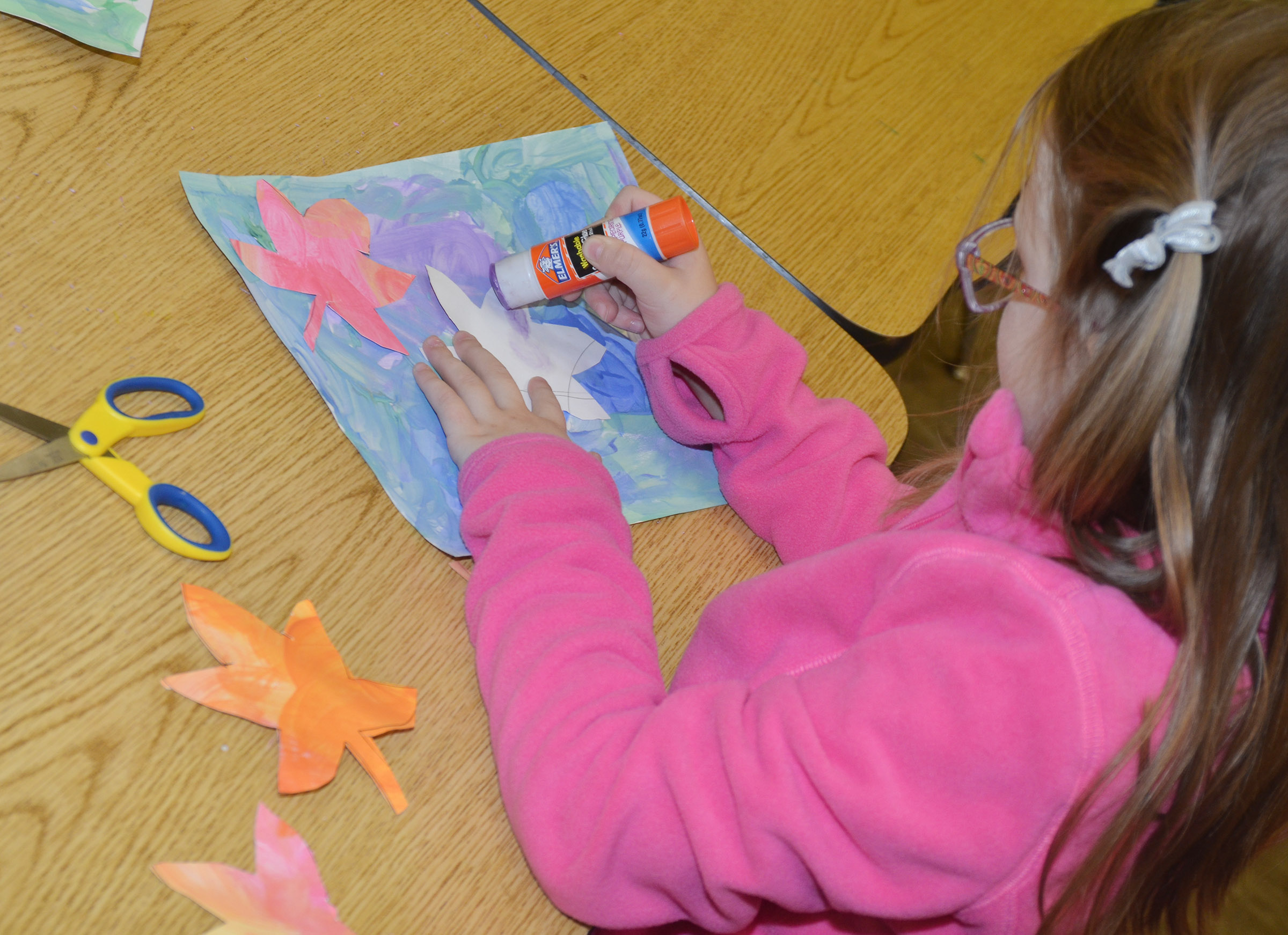 CES kindergartener Emmaline Vespie glues her leaves to her cool color painting.