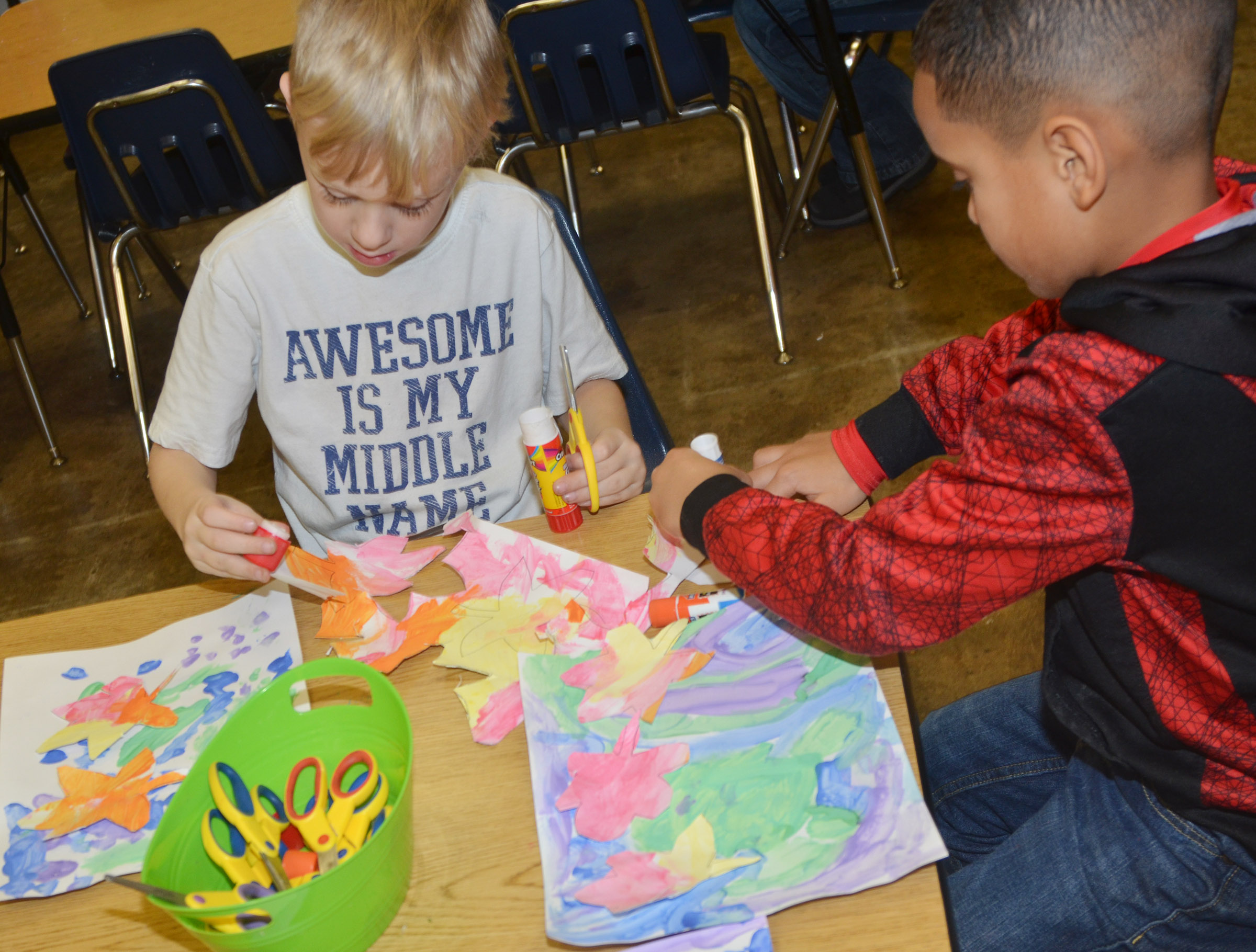 CES kindergarteners Lukas Adams, at left, and Kingston Cowherd cut out their leaves and glue them to their cool color paintings.