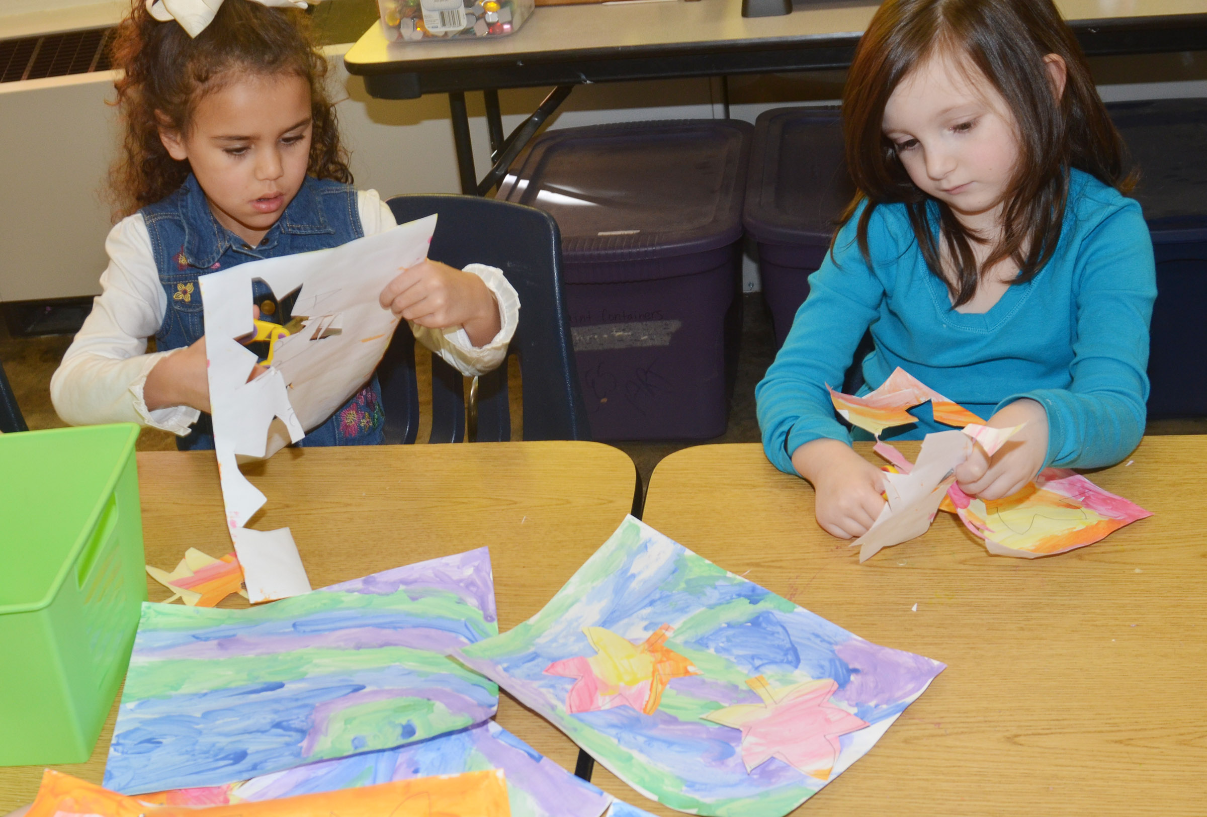 CES kindergarteners Adelyn Litsey, at left, and Abigail Smith cut out their leaves and glue them to their cool color paintings.
