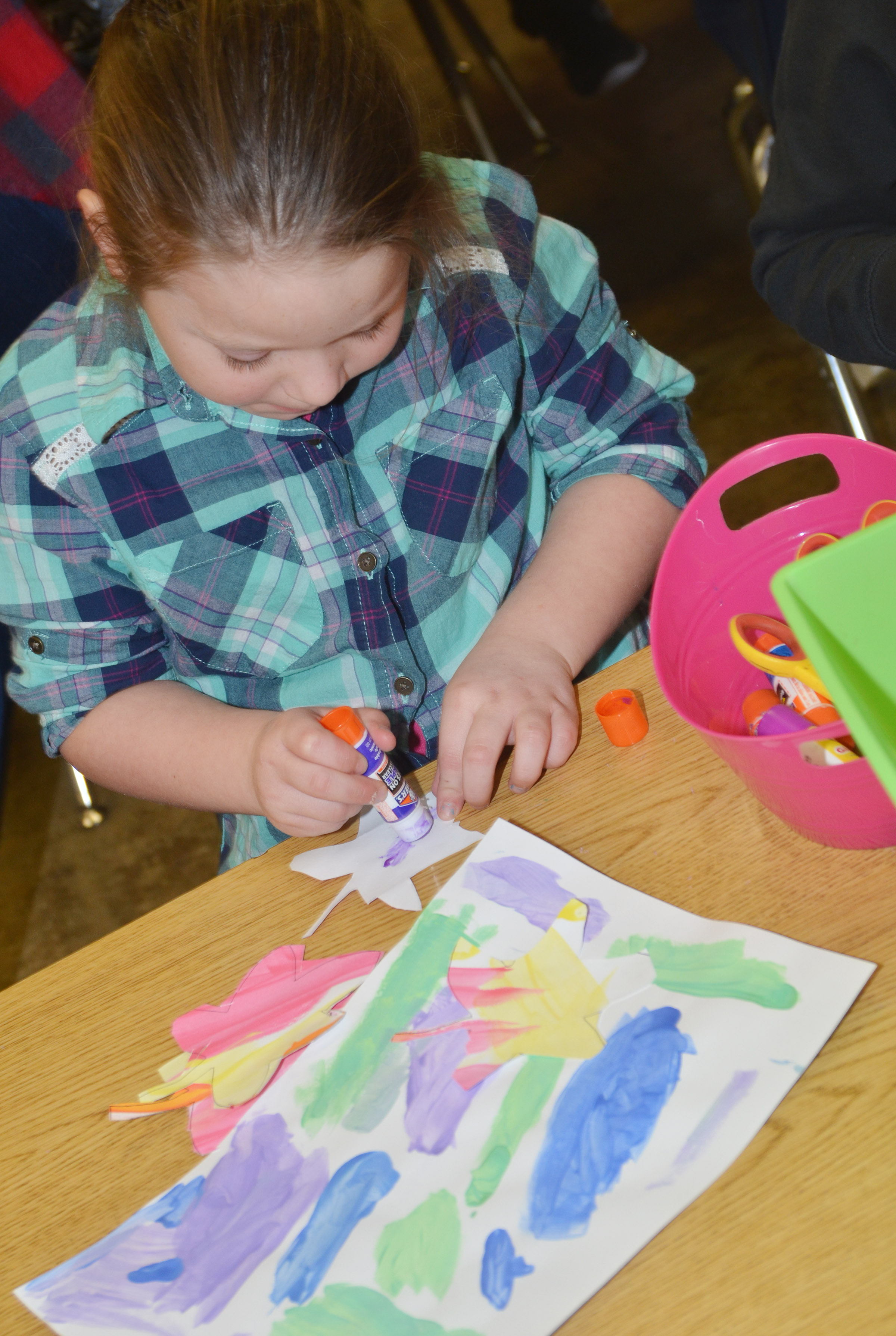 CES kindergartener Gracie McKenzie glues her leaves to her cool color painting.