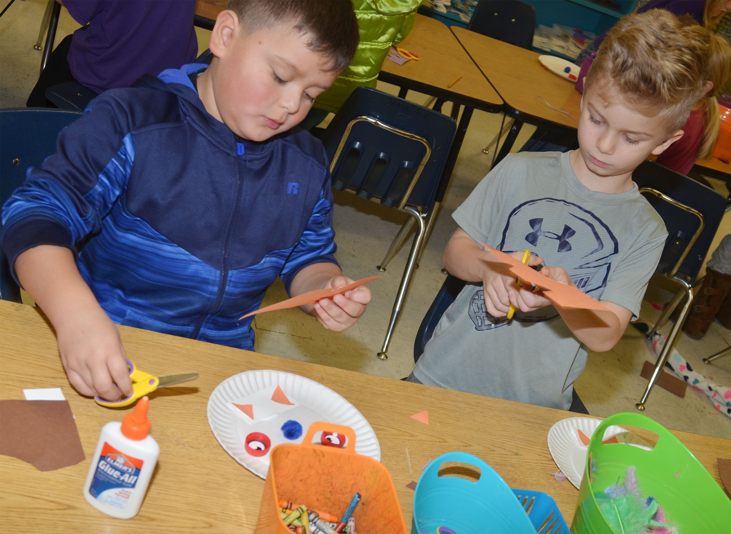 CES first-graders Alex Mixtega, at left, and Parker Hamilton cut out construction paper for their monsters.