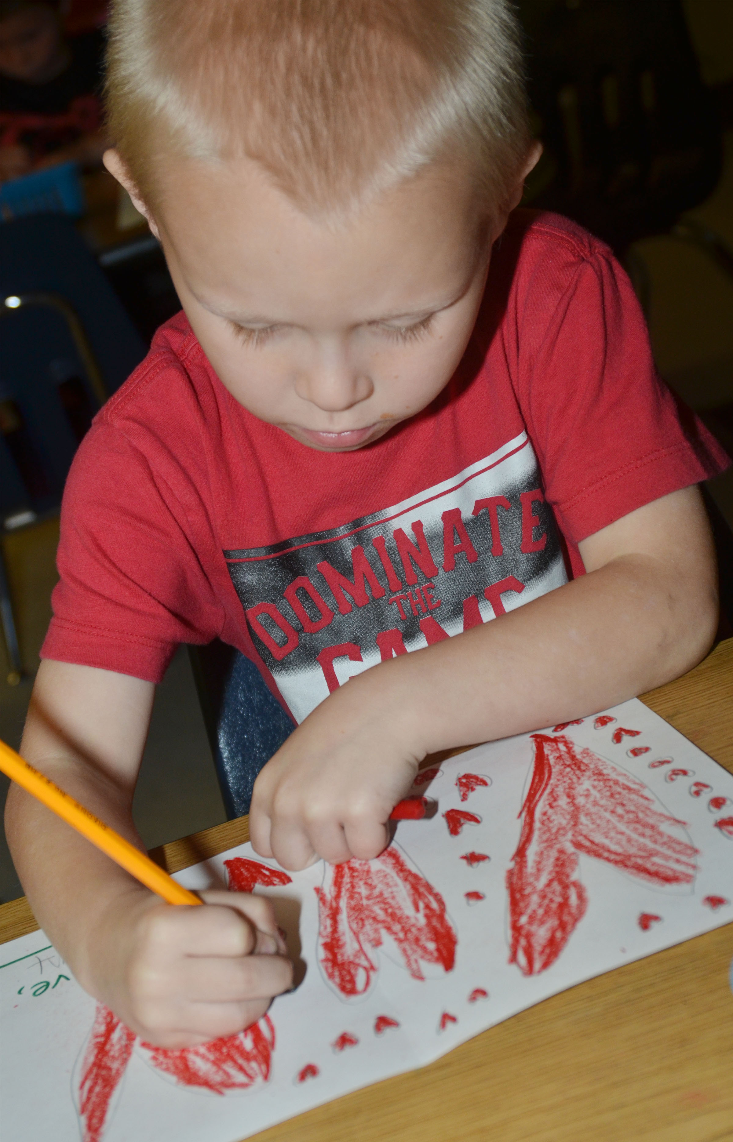 CES kindergartener Robert Atwood draws hearts on his Mother's Day card.