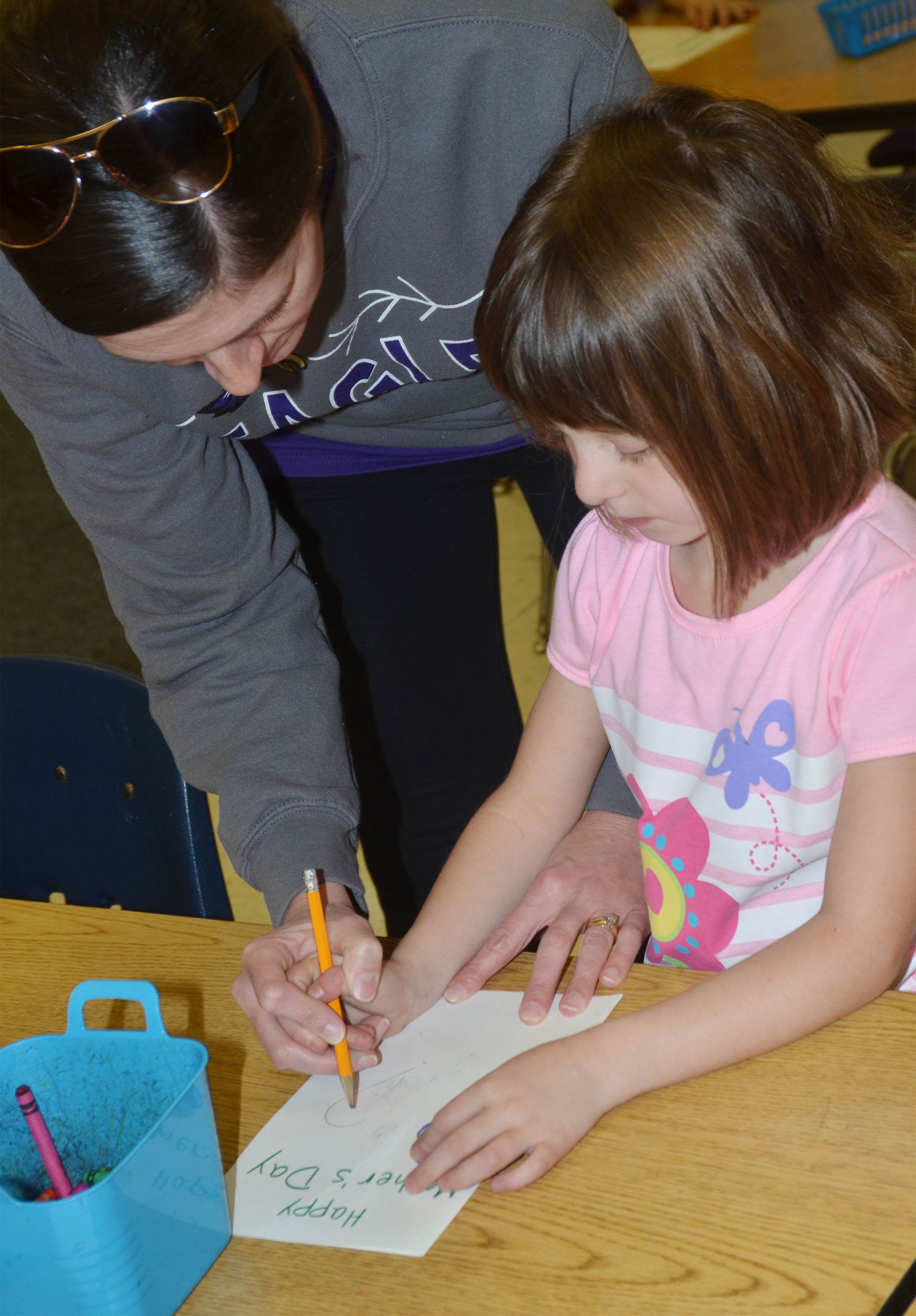 CES art teacher Adrienne Hash helps kindergartener Serenity Bell draw a heart on her Mother's Day card.