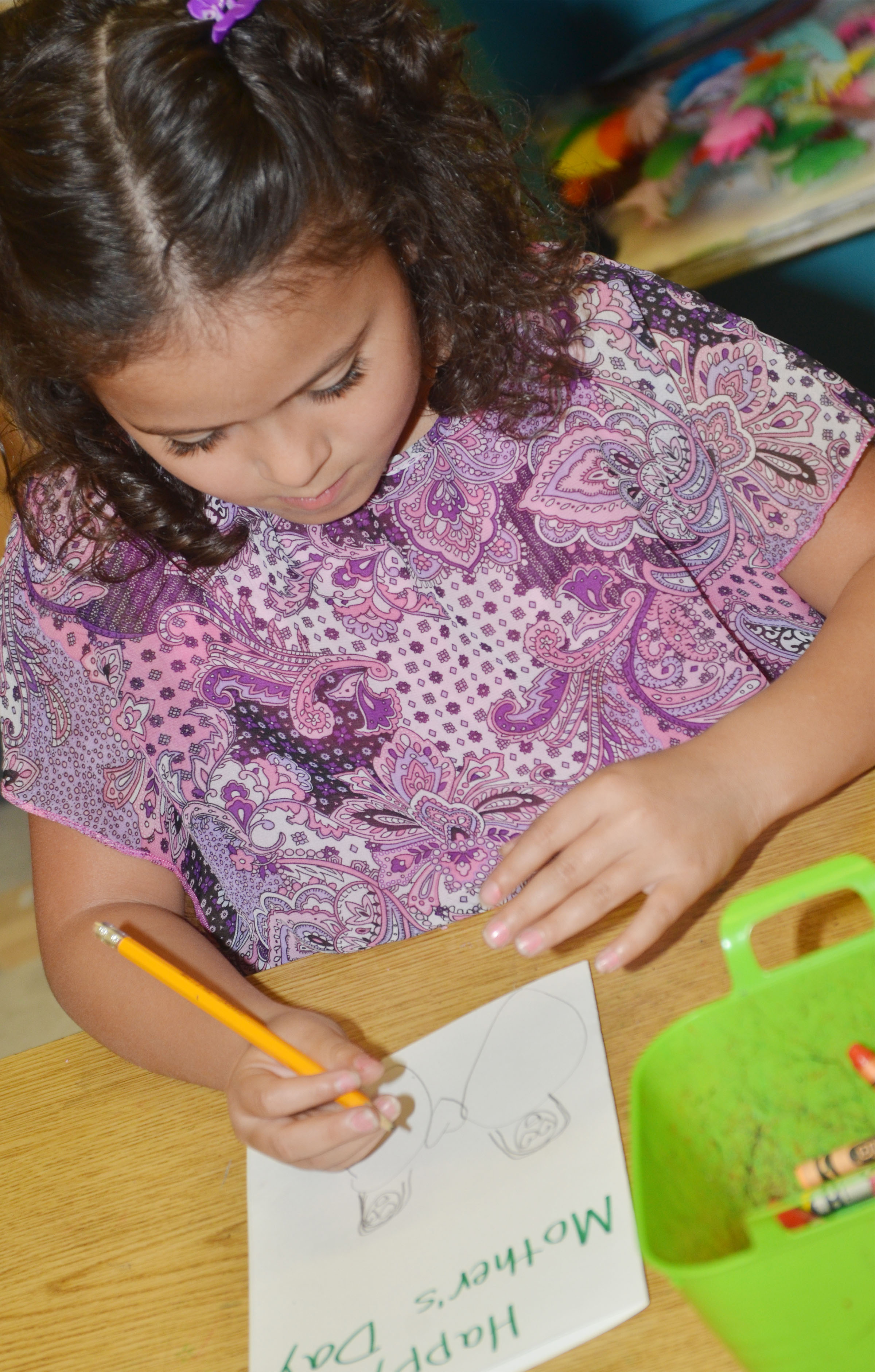 CES kindergartener Isabella Anderson draws on her Mother's Day card.