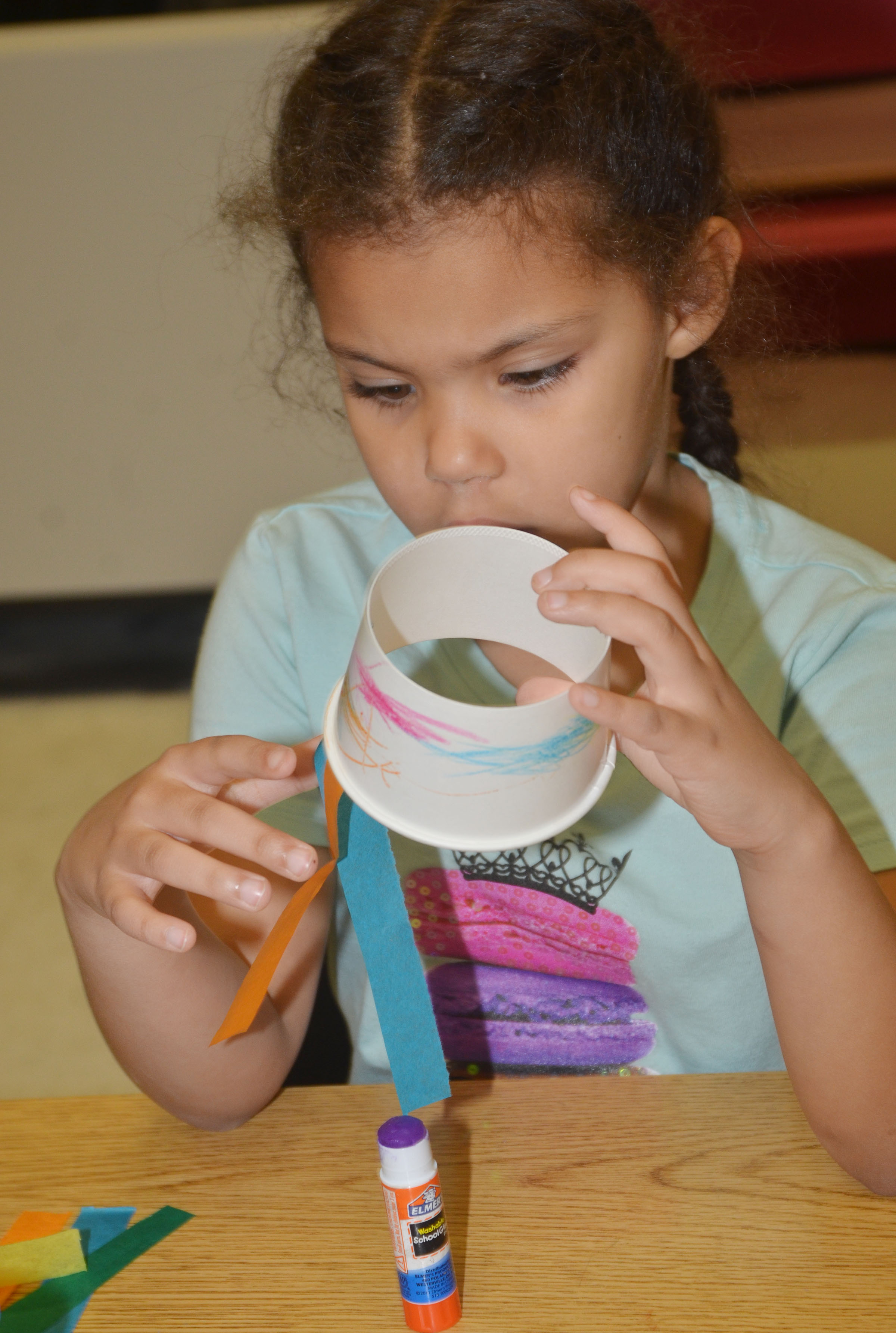 CES kindergartener Jasymon Musselwhite glues tentacles on her octopus.