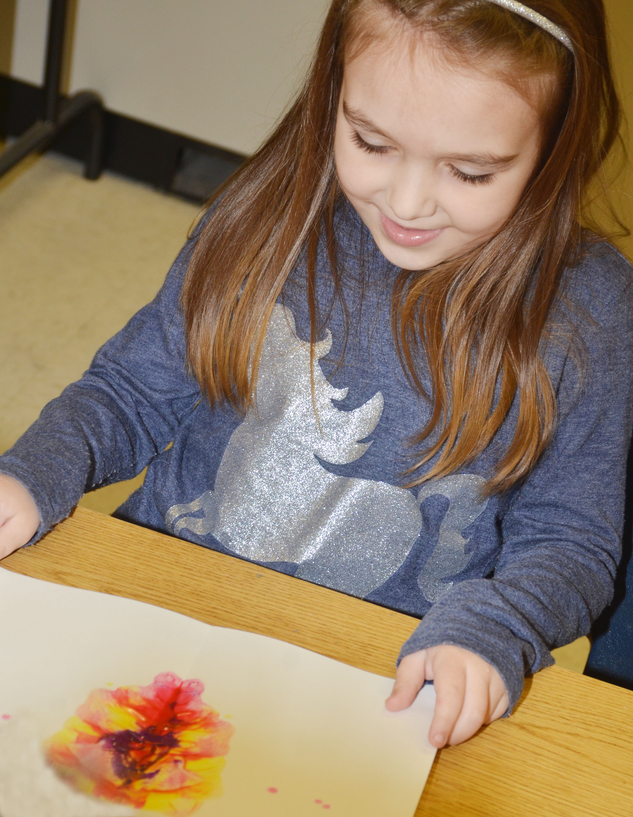 CES kindergartener Aubrey Allen smiles as she opens her monoprint.