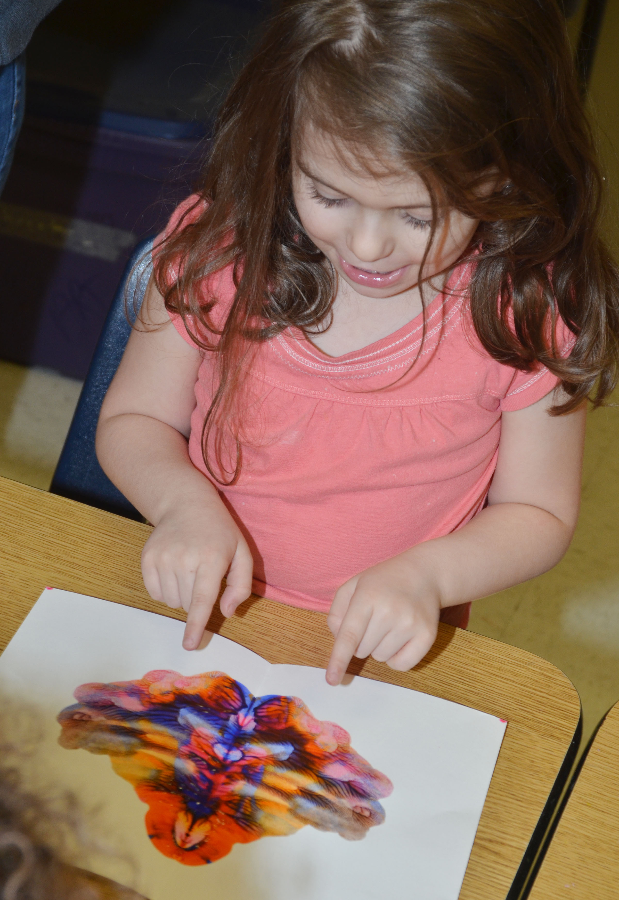 CES kindergartner Addison Beckley looks at her monoprint.