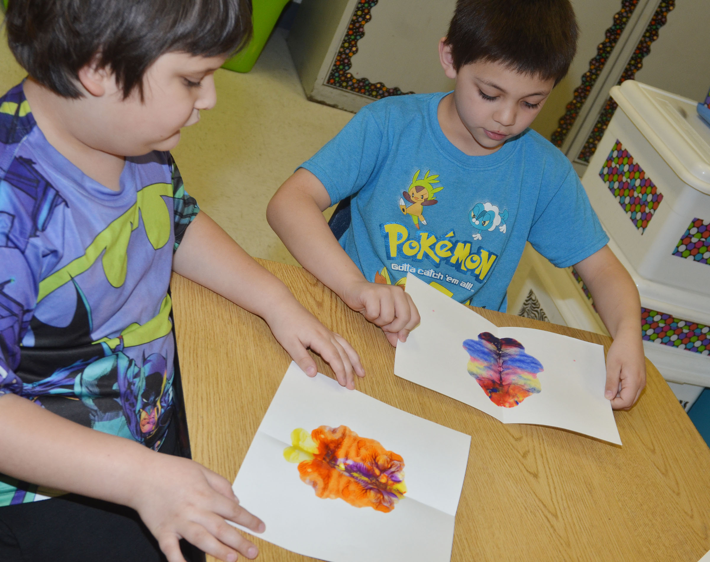 CES kindergarteners Cloud Malone, at left, and Keagan Shearer open their monoprints.