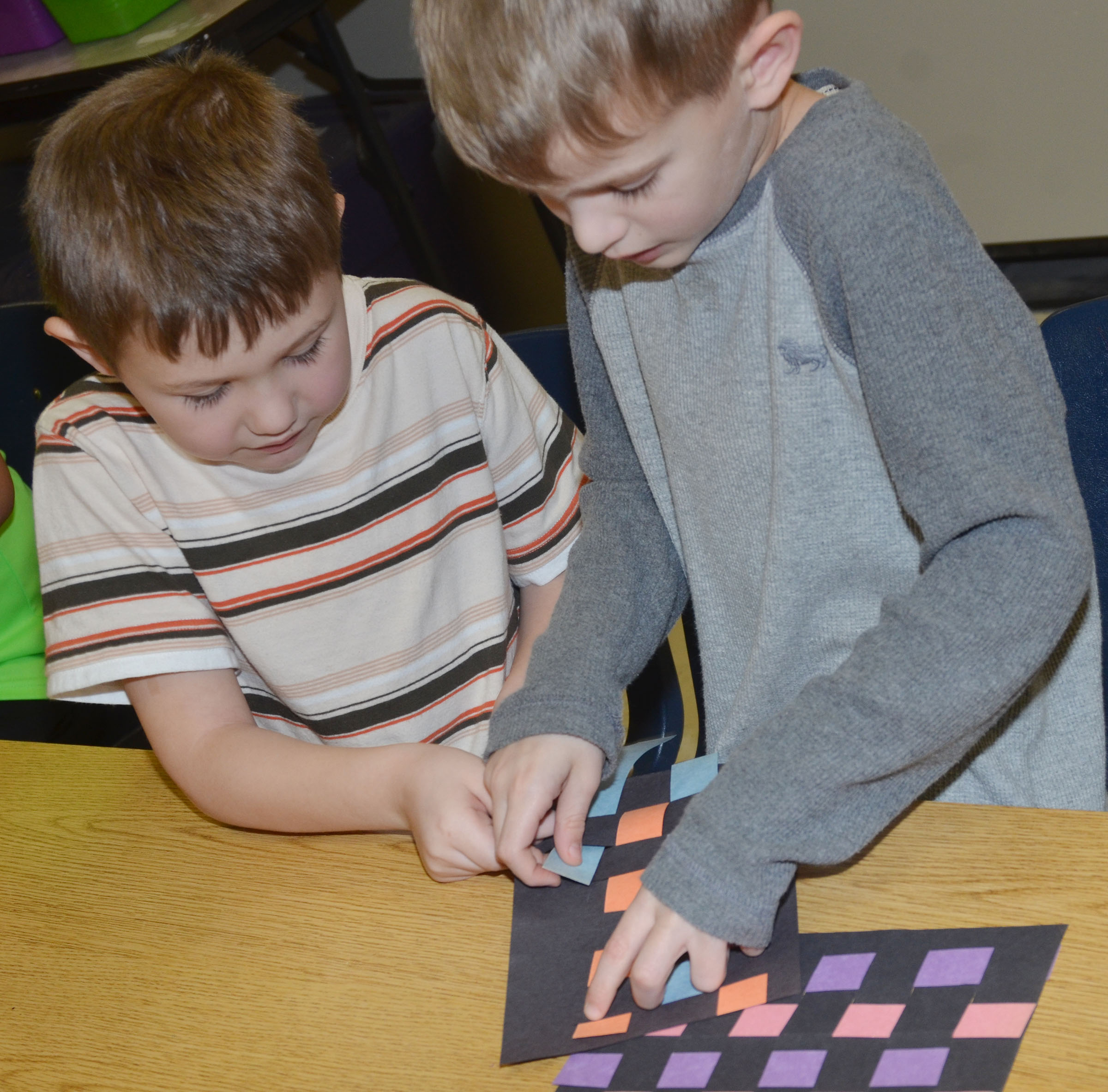 CES first-grader Logan Weddle, at right, helps classmate Lucan Abel weave his mat.