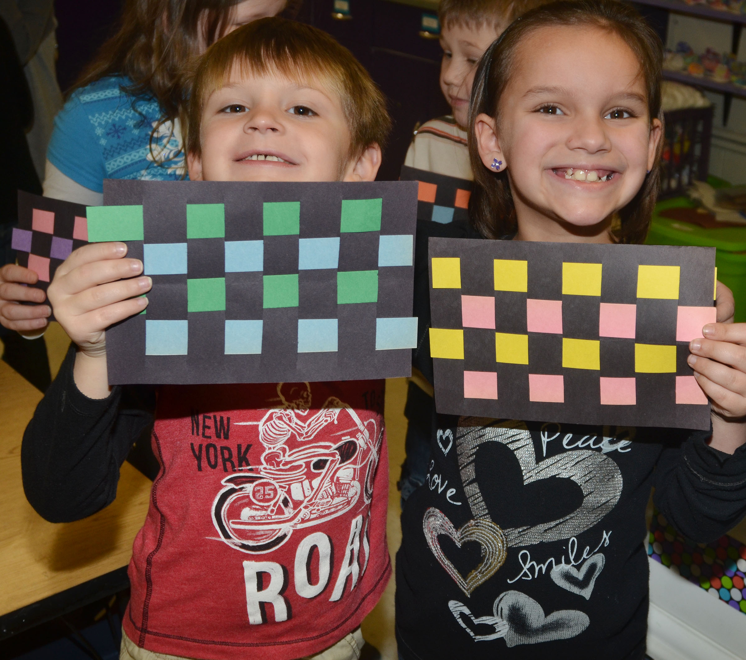 CES first-graders Seeley Whitaker, at left, and Adriana Agent hold their finished mats.