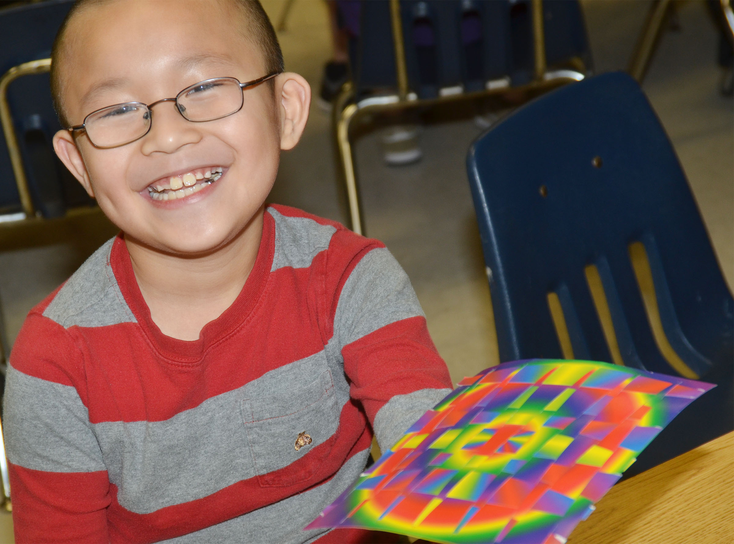 CES second-grader Alex Yang holds his finished paper weaving.
