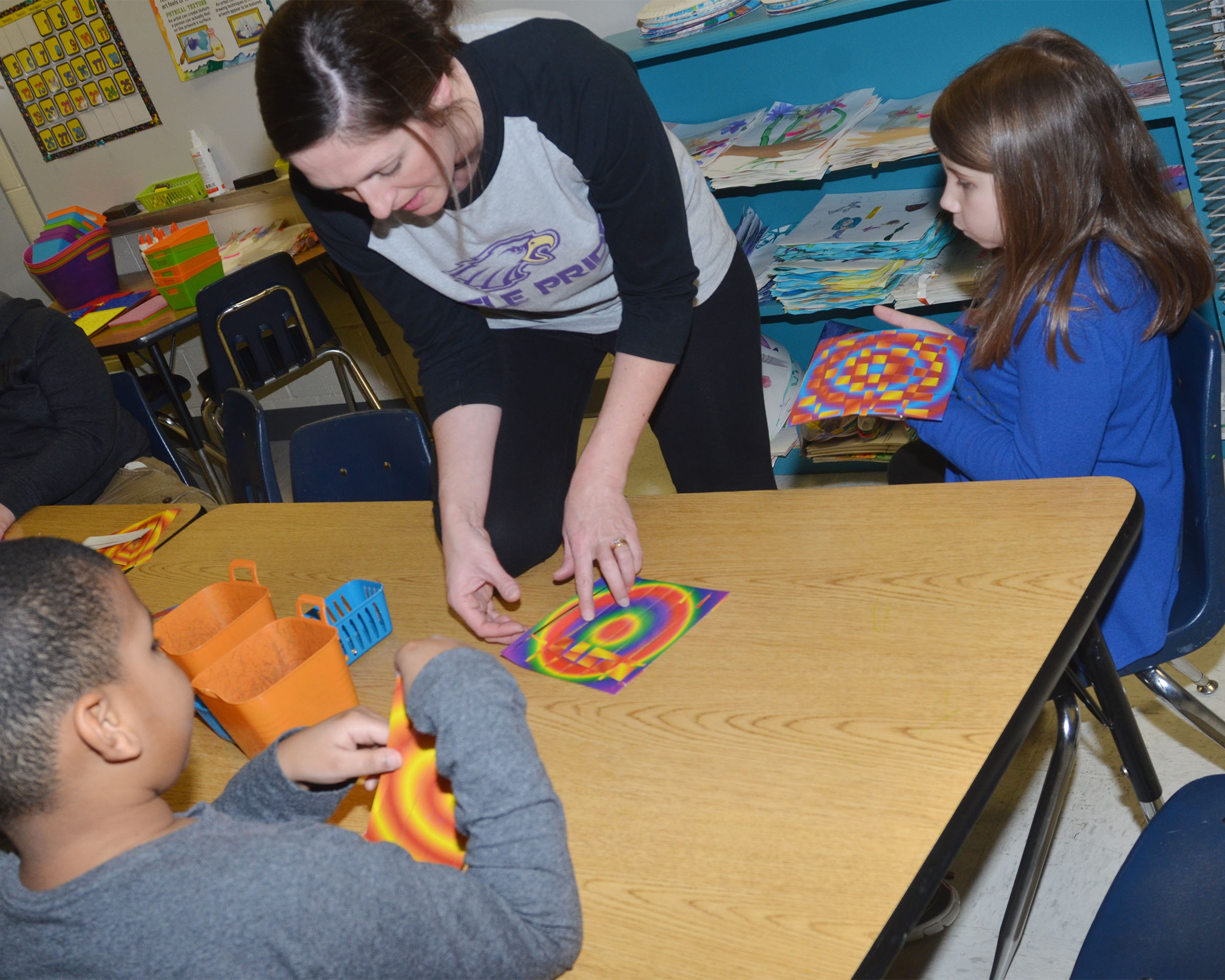 CES art teacher Adrienne Hash helps CES second-graders Zaemar Hoskins, at left, and Natalia West with their paper weaving.