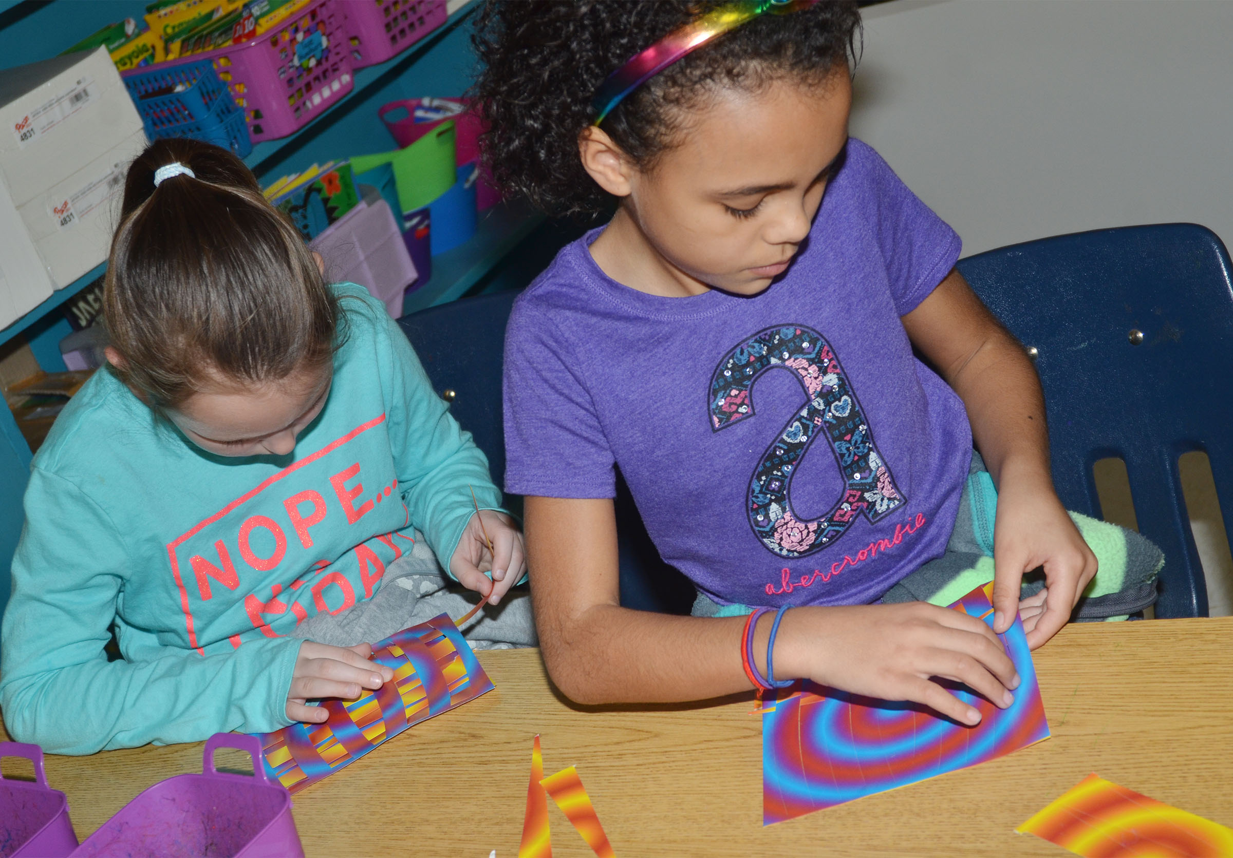 CES second-grader River McFarland, at left, and Braelyn Taylor weave their papers together.