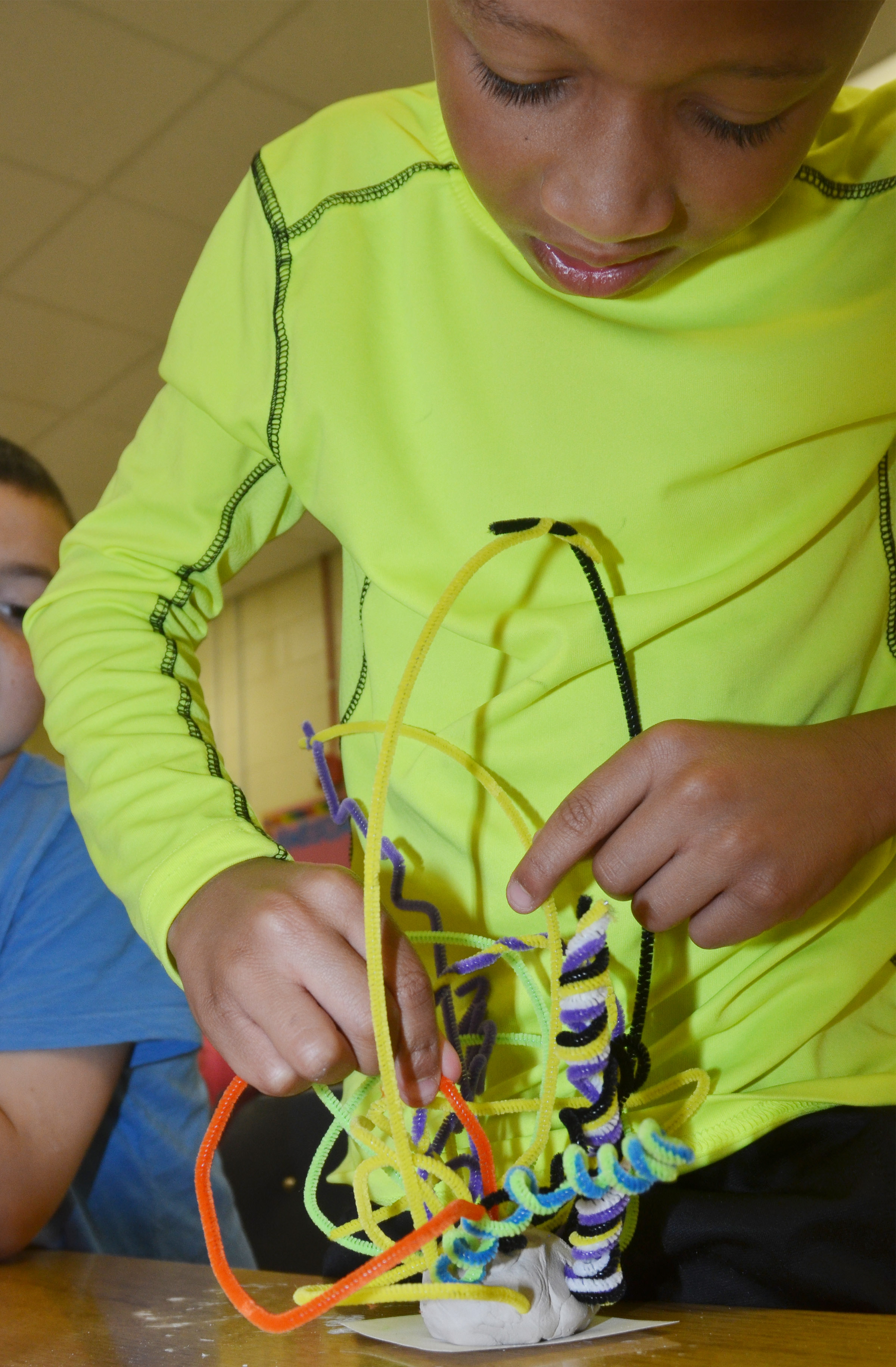 CES second-grader Rajon Taylor concentrates as he builds his pipe cleaner sculpture.