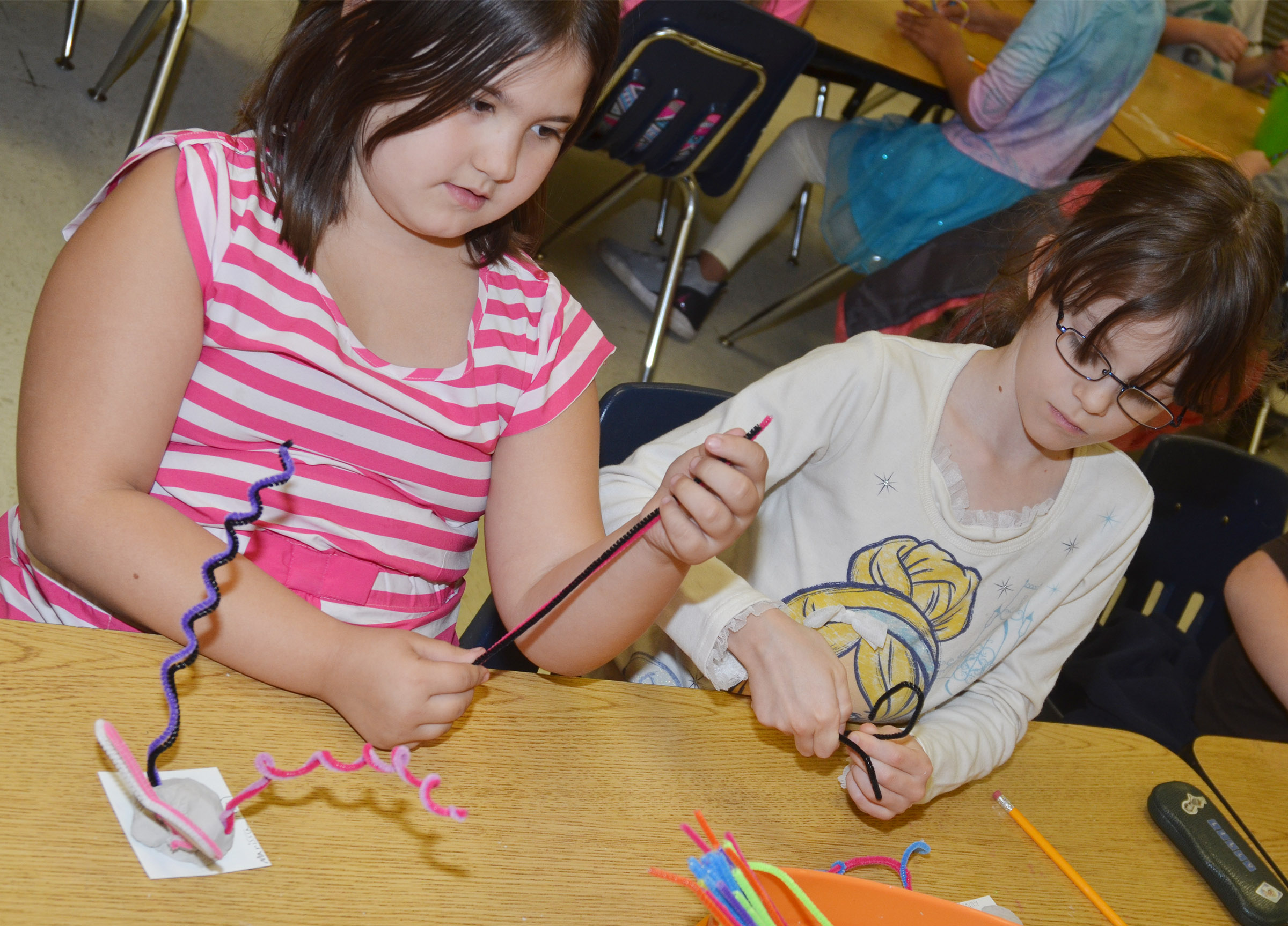 CES second-graders Marissa Sumners, at left, and Lilly Wise shape their pipe cleaners.