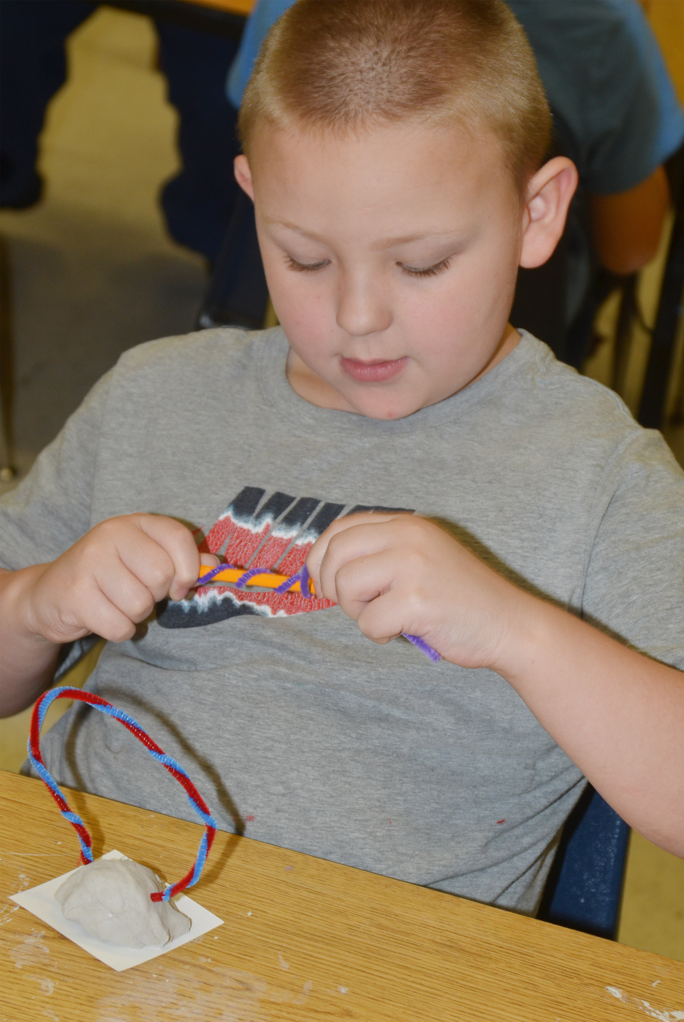 CES second-grader Peyton Mitchell twists his pipe cleaner around his pencil.