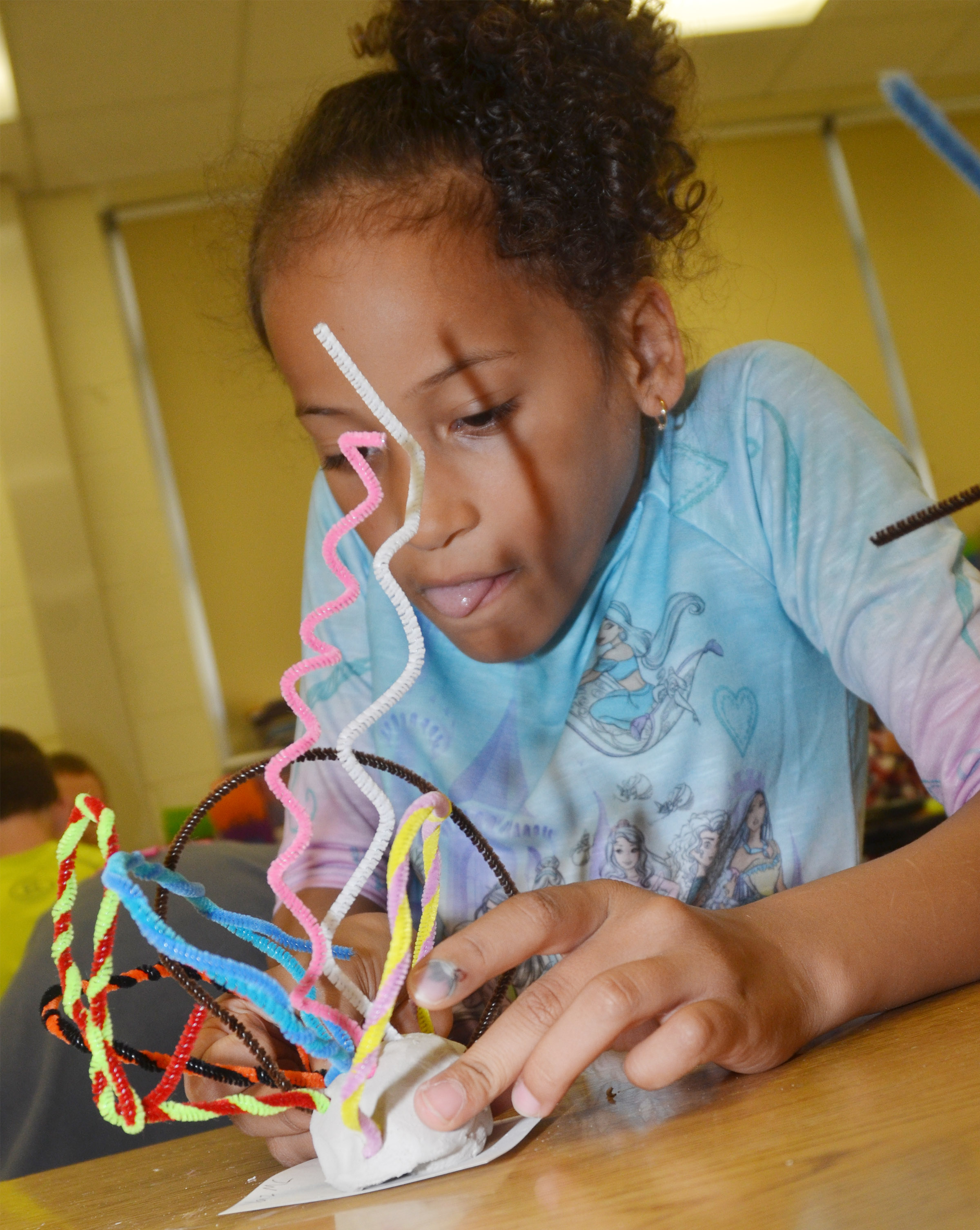 CES second-grader Yazlyn Sutton concentrates as she builds her pipe cleaner sculpture.