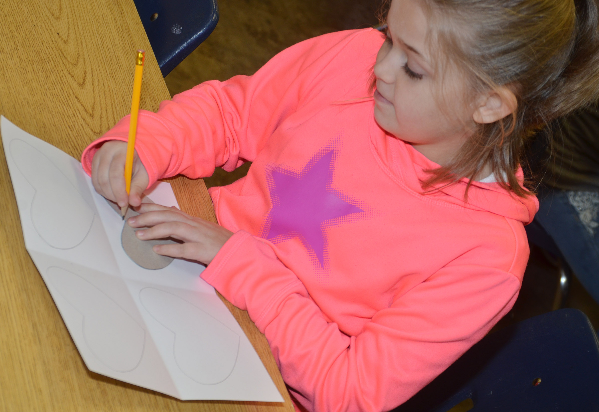 CES fourth-grader Chyanne Christie traces a heart as she makes her pop art.
