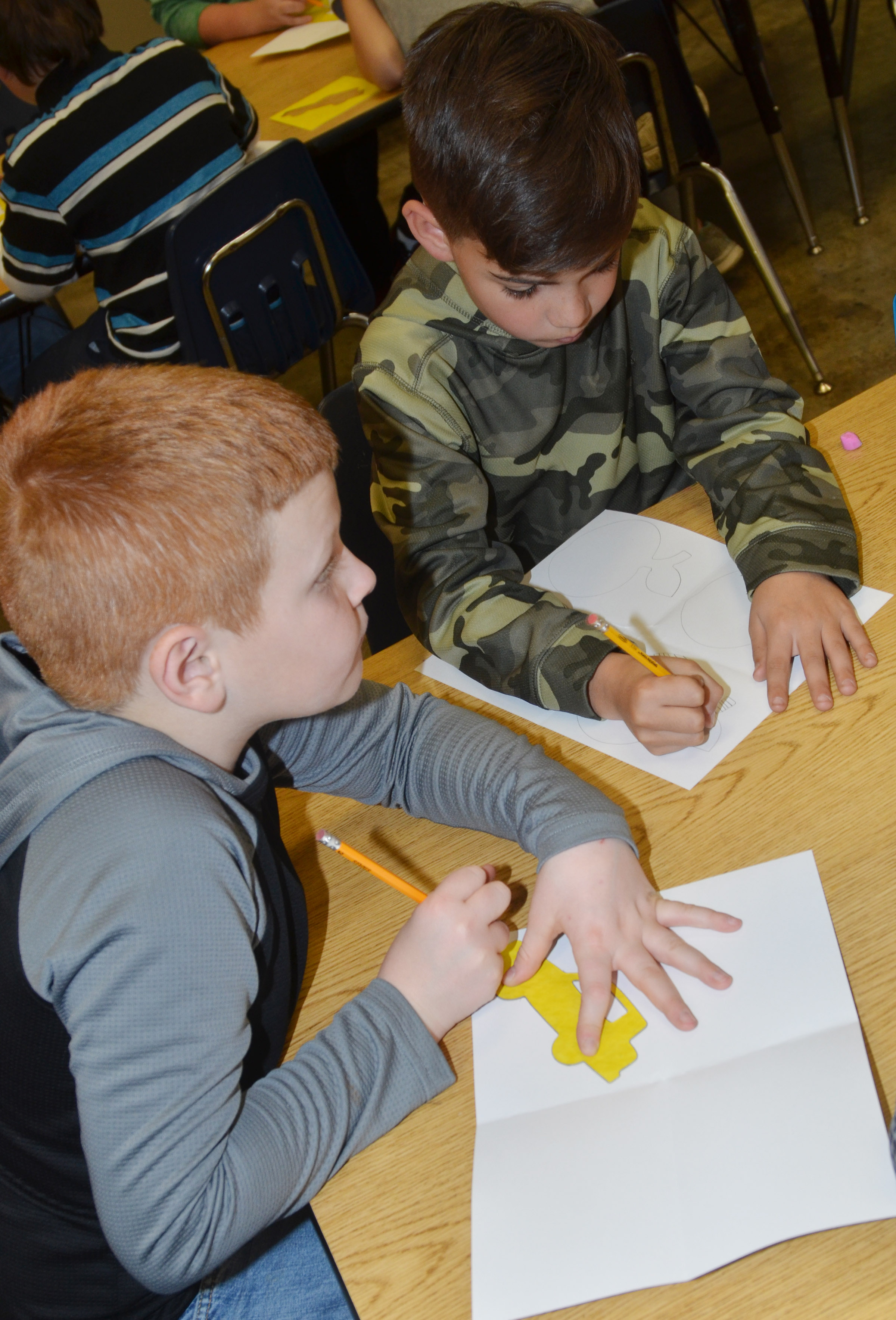 CES fourth-graders Westin Dudgeon, at left, and Easton Williams trace their stencils as they make their pop art.