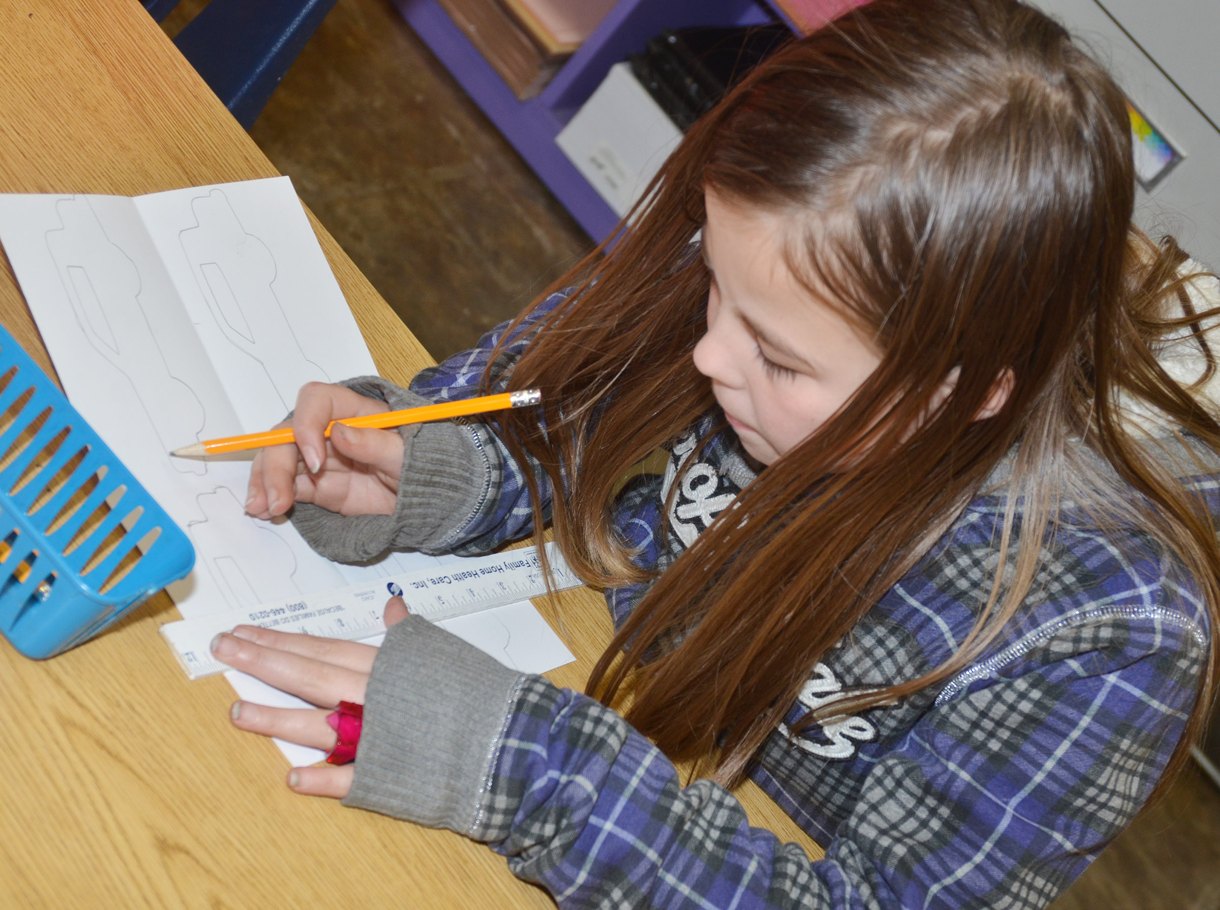 CES fourth-grader Chloe Bates traces a stencil as she makes her pop art.