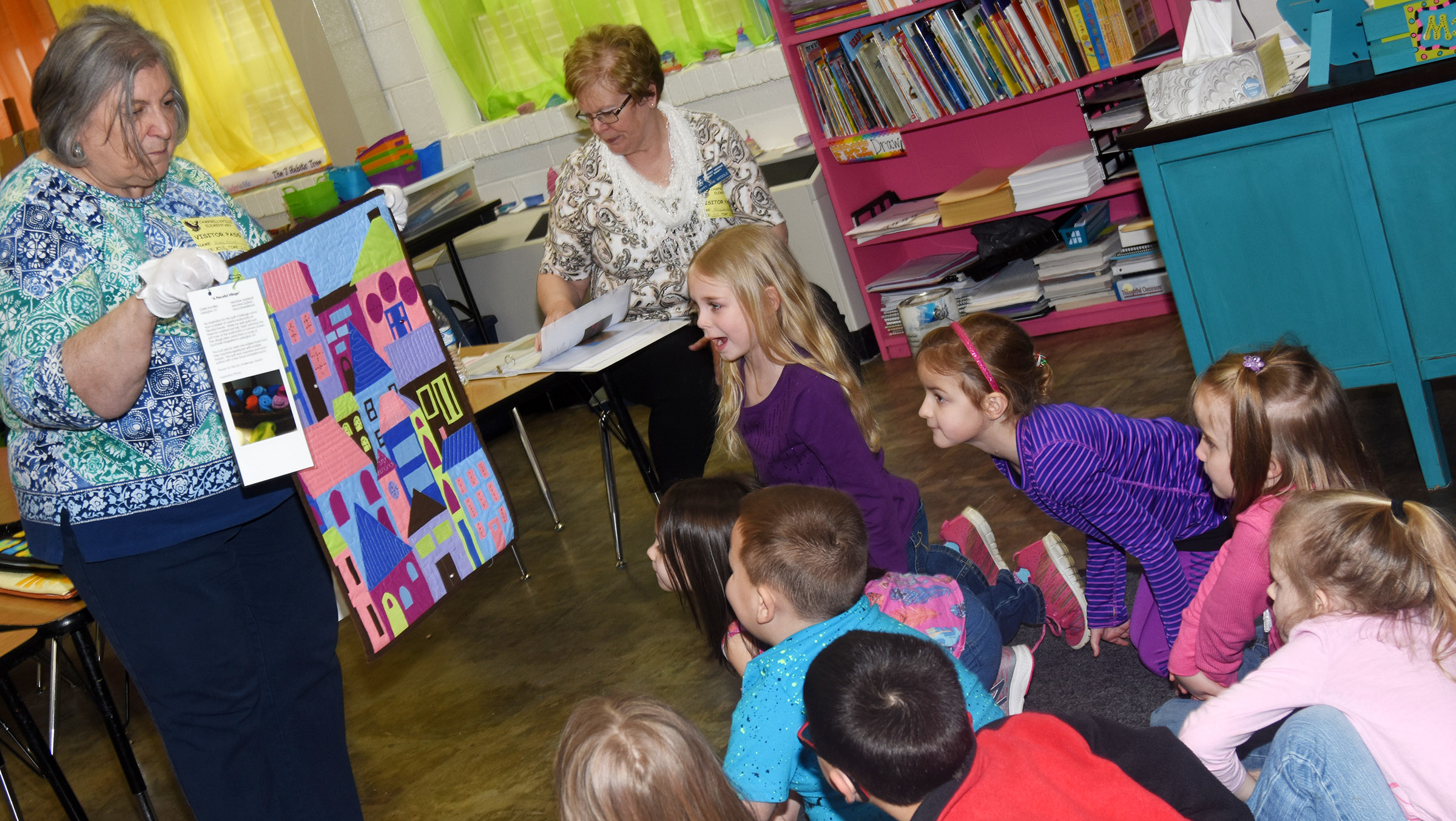 Mary Street, at left, and Mary Jane Weddle from the Kentucky Heritage Quilt Society talk to CES kindergarteners about how quilts are made.