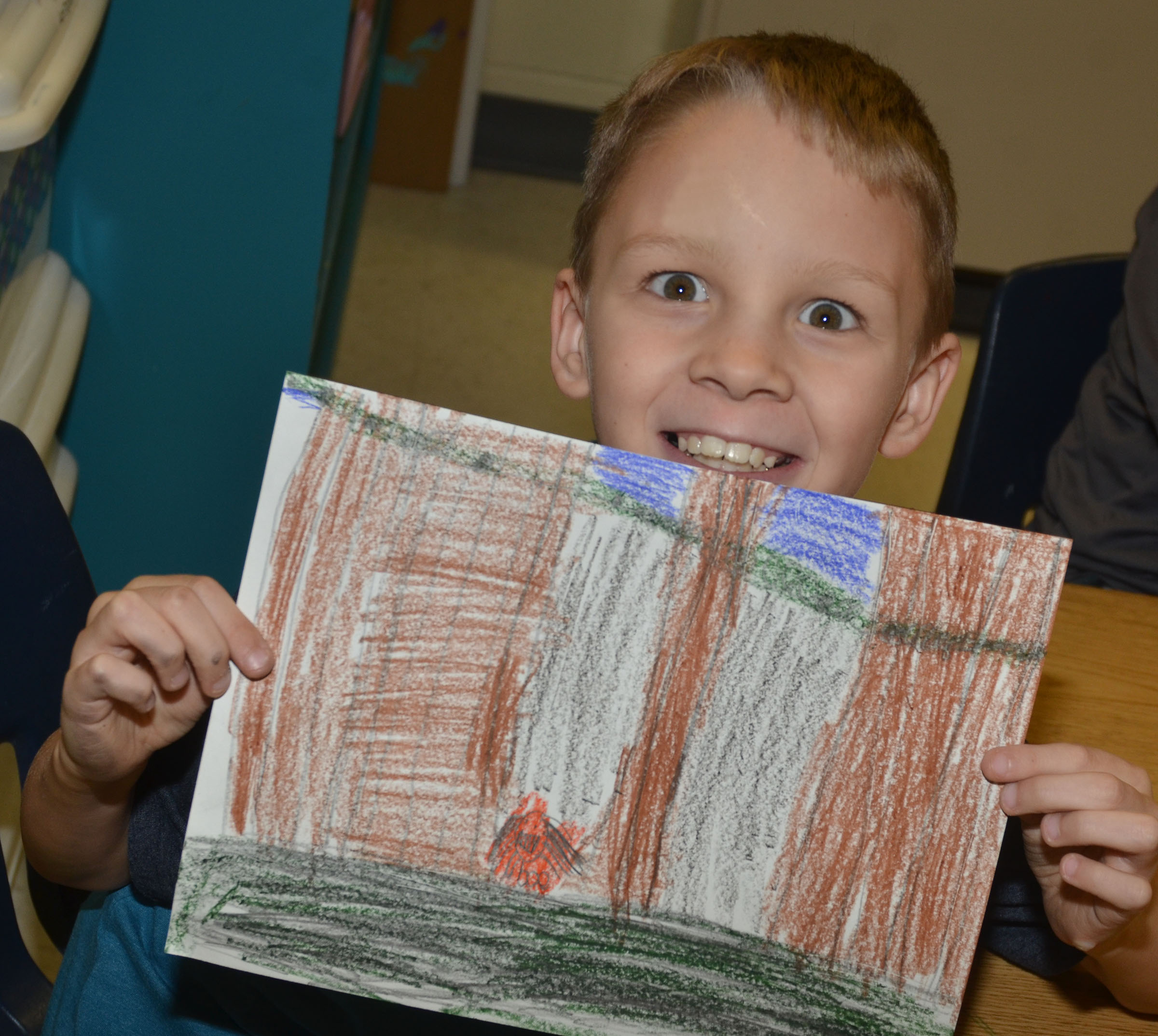 CES second-grader Braxton Agee holds his finished rainforest drawing.