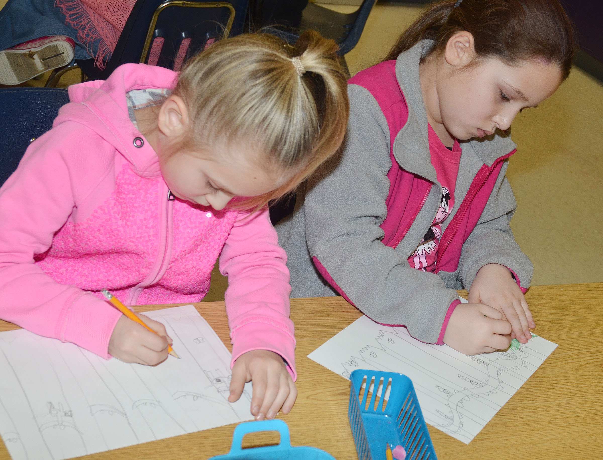 CES second-graders Ava Ellis, at left, and Keely Rakes work on their rainforest scenes.