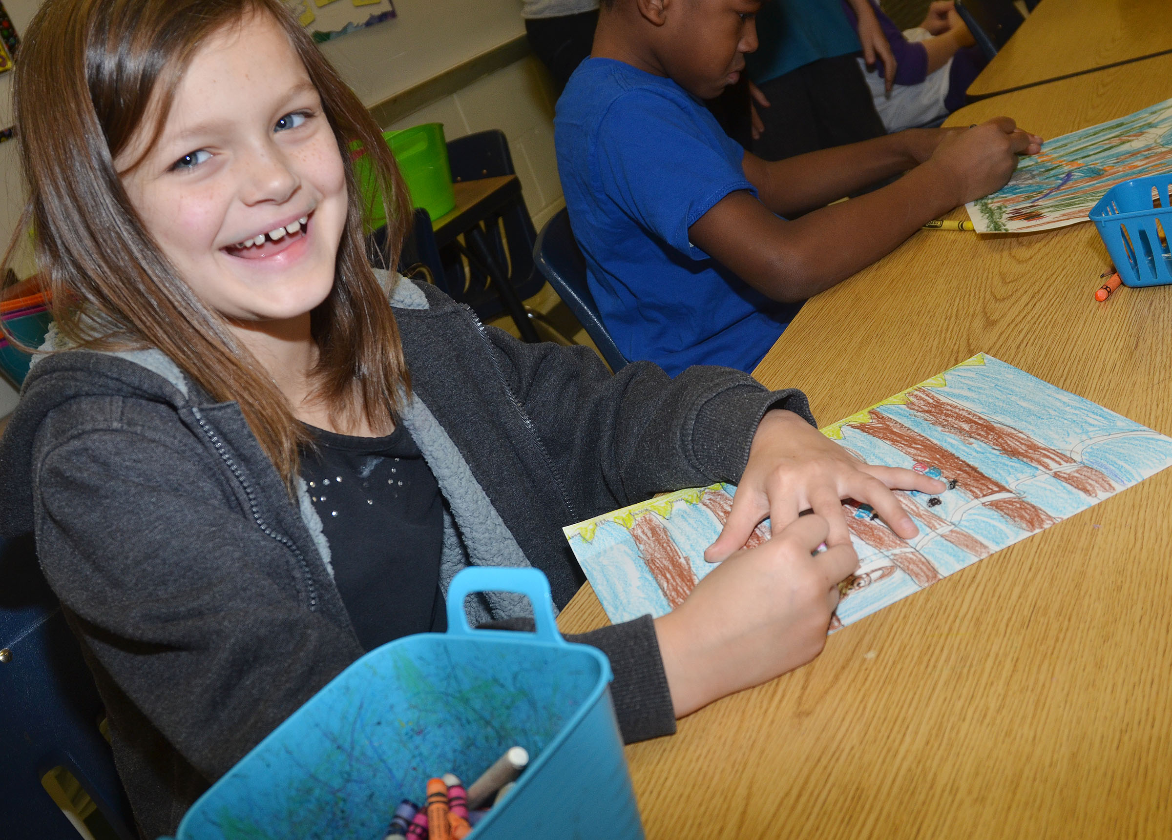 CES second-grader KayLee Lamer smiles as she colors her rainforest scene.