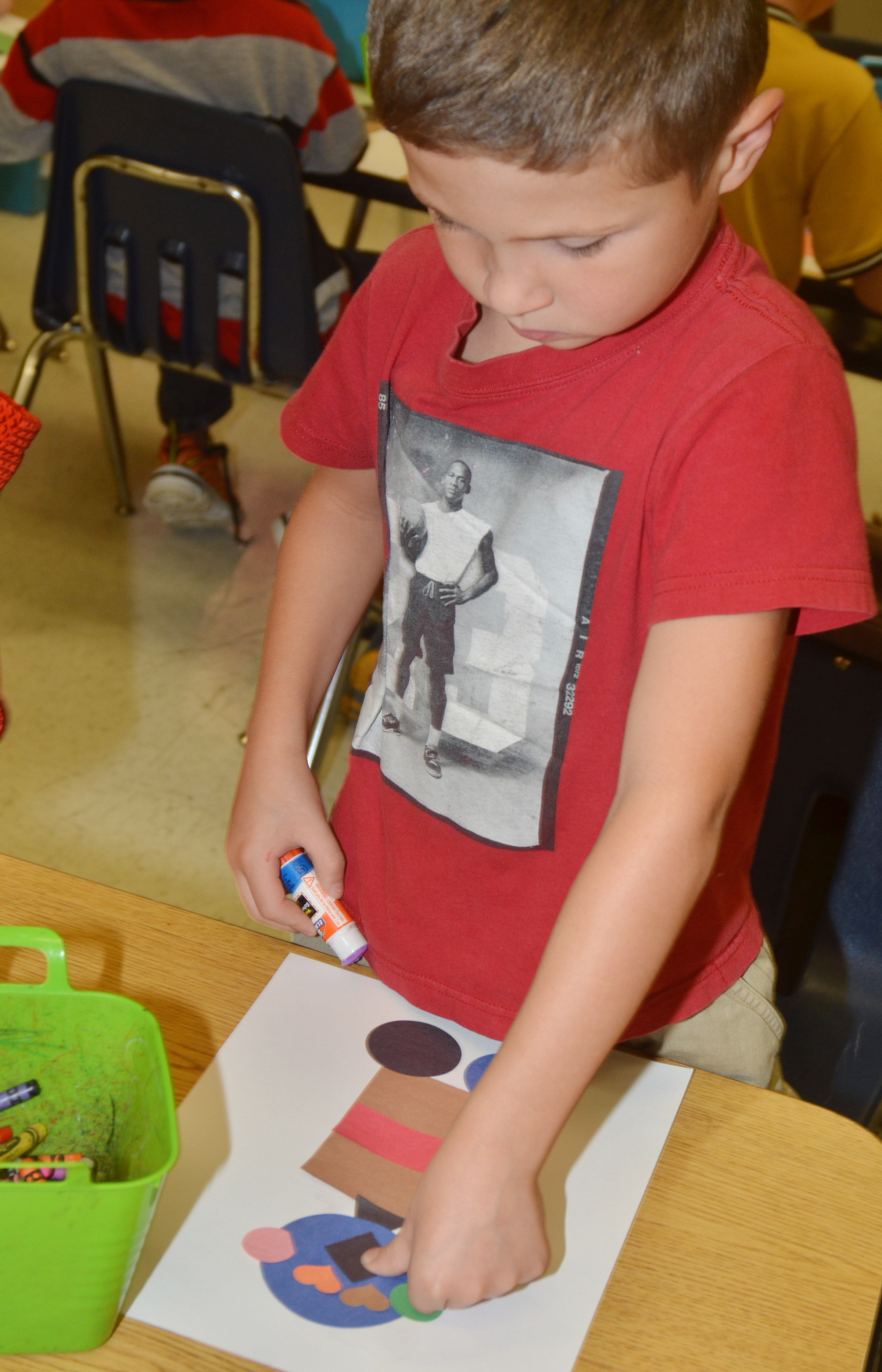 CES second-grader Bryson Gabehart glues his robot together.