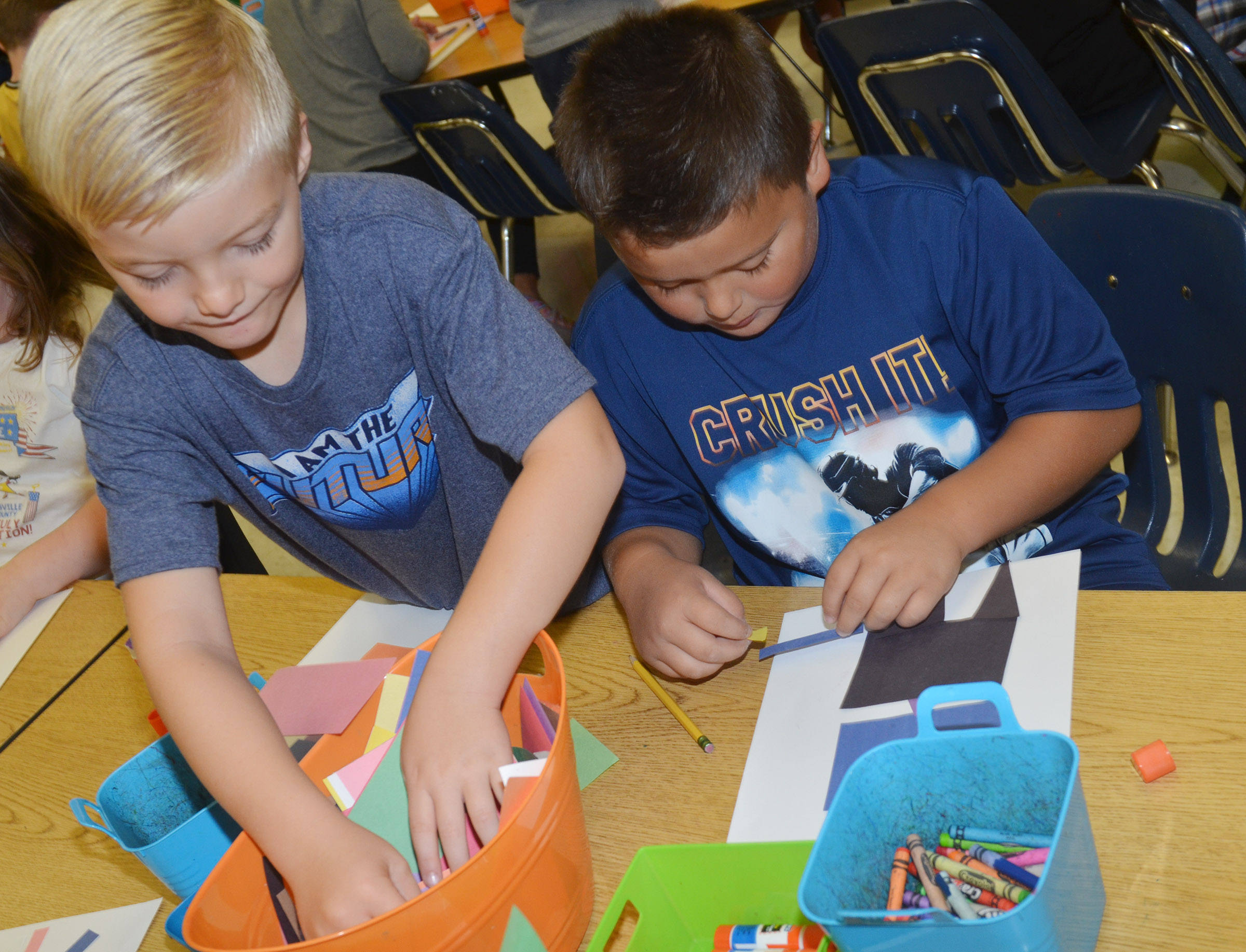 CES second-graders Parker Scharbrough, at left, and Alex Mixtega glue their robots together.