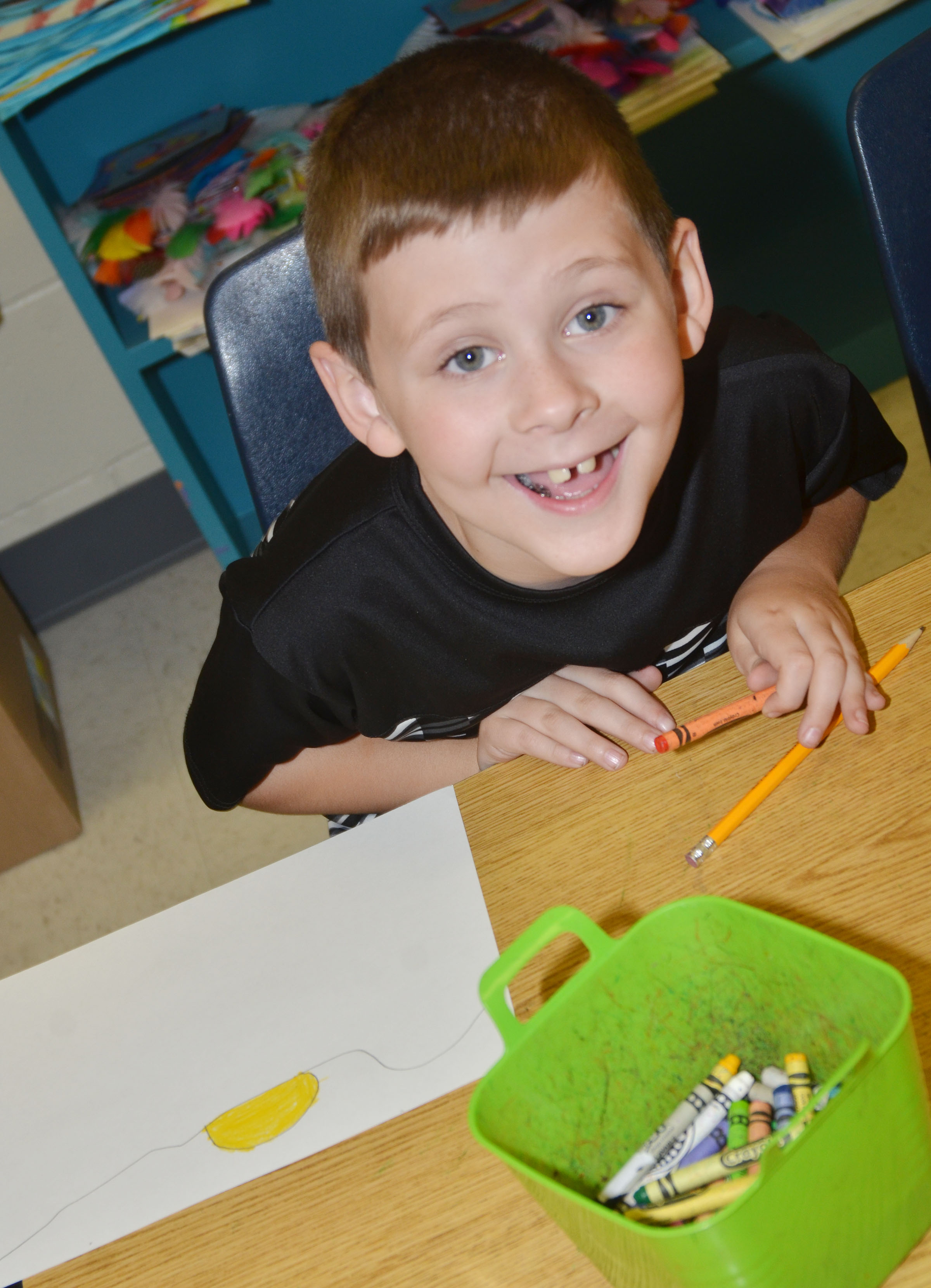 CES second-grader Ryan Tungate smiles as he works on his Save the Frogs contest artwork.