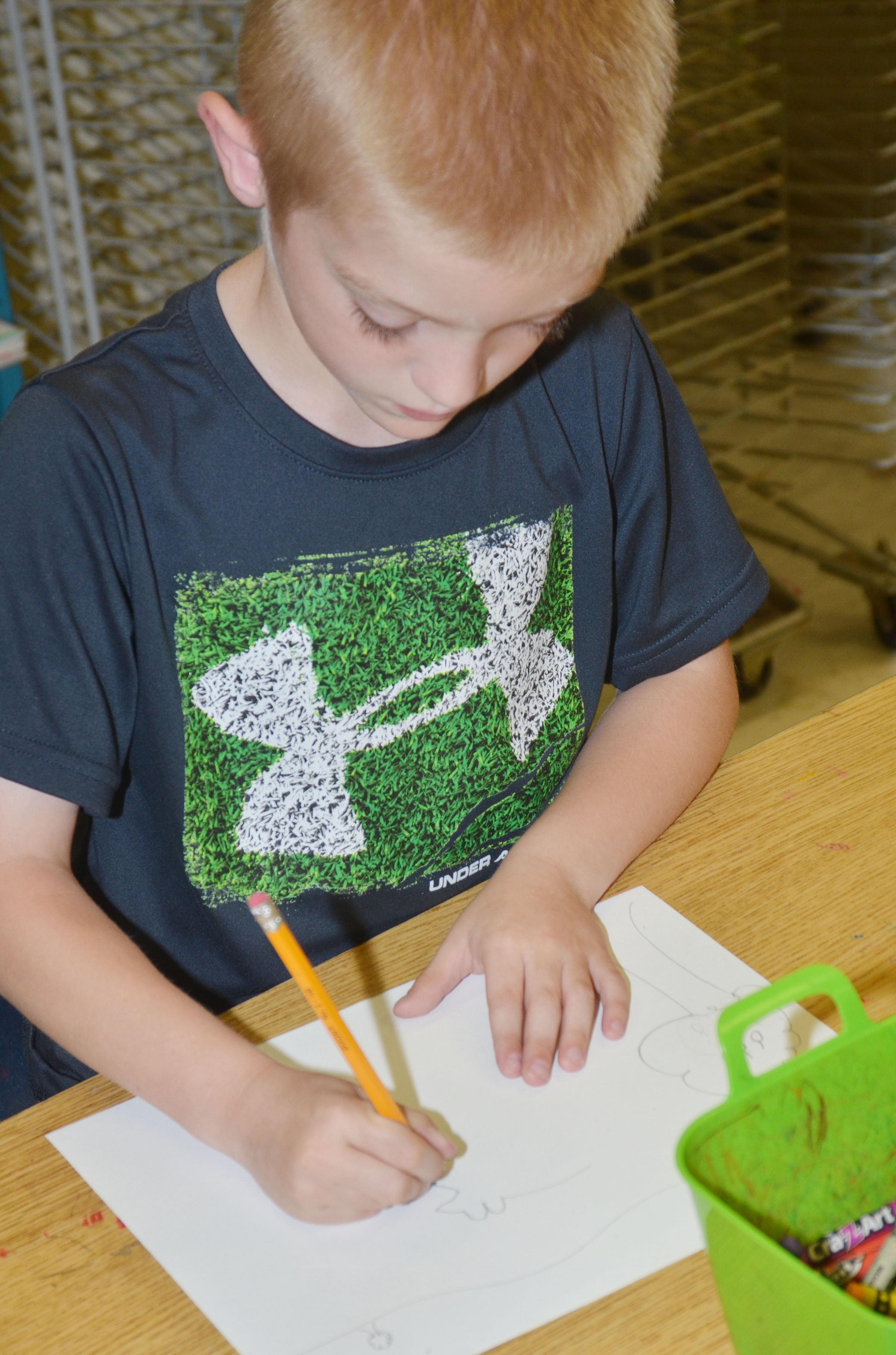 CES second-grader Evan Cundiff draws his frog scene for the Save the Frogs contest.