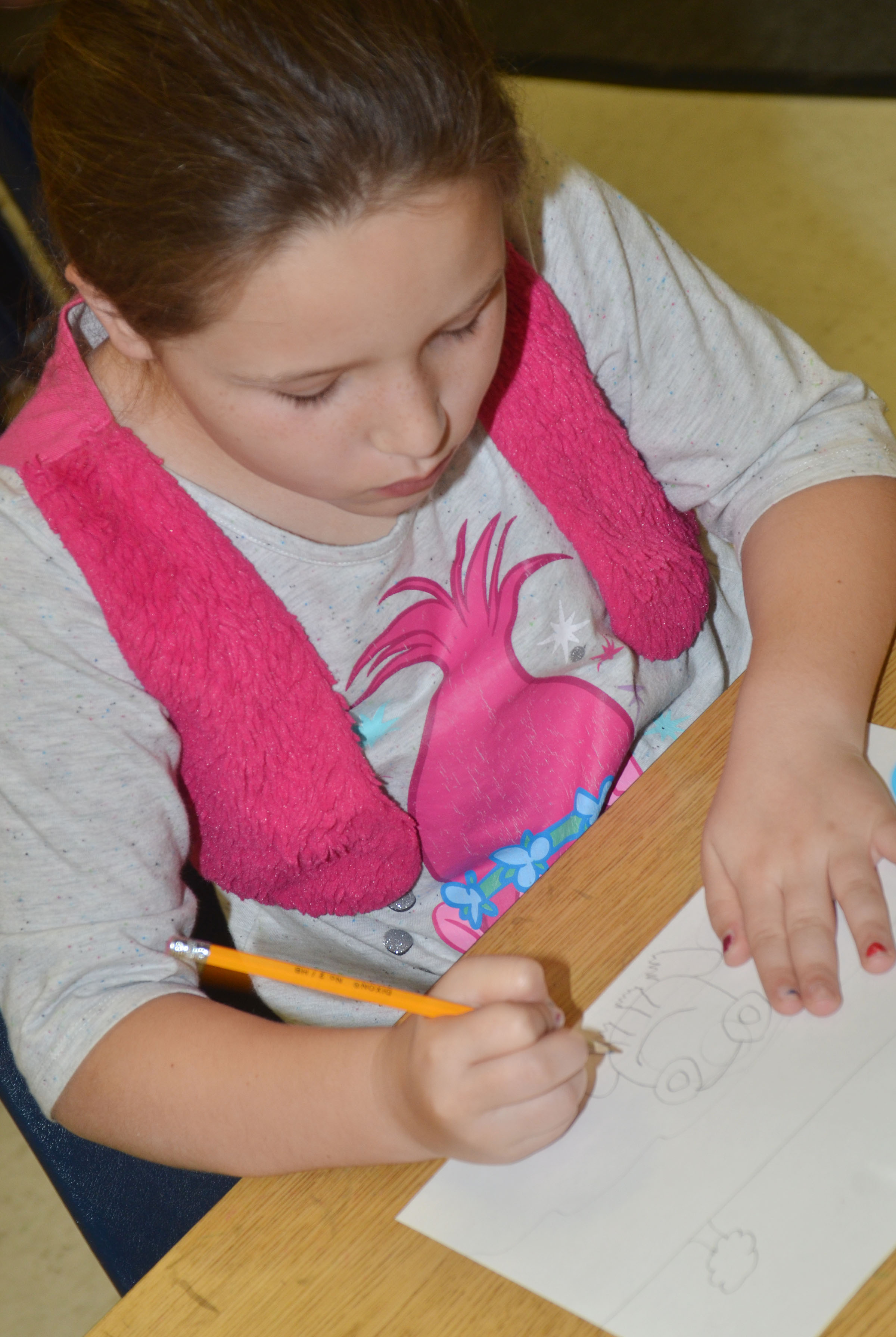 CES second-grader Keely Rakes draws her frog scene for the Save the Frogs contest.