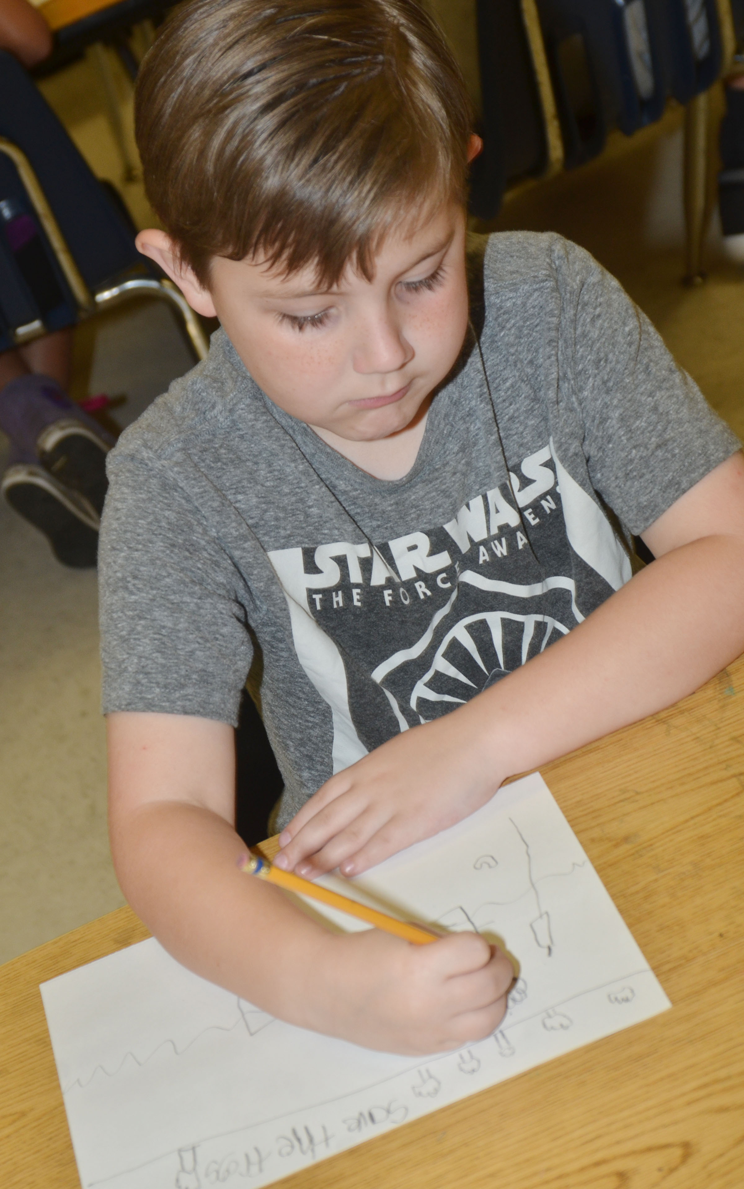 CES second-grader Seamus Huber draws his frog scene for the Save the Frogs contest.