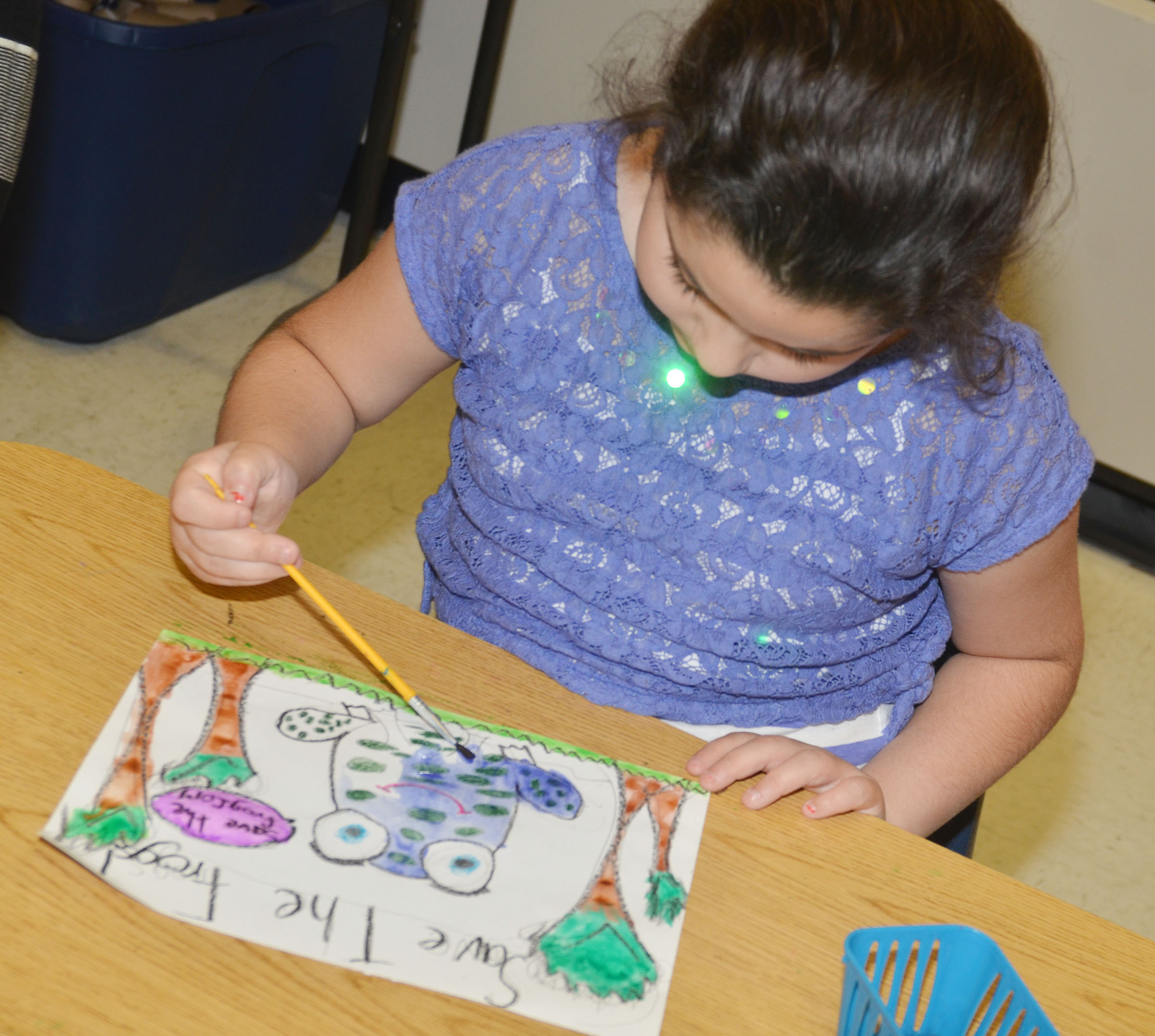 CES third-grader Brooklyn Boudreaux paints her Save the Frogs artwork.