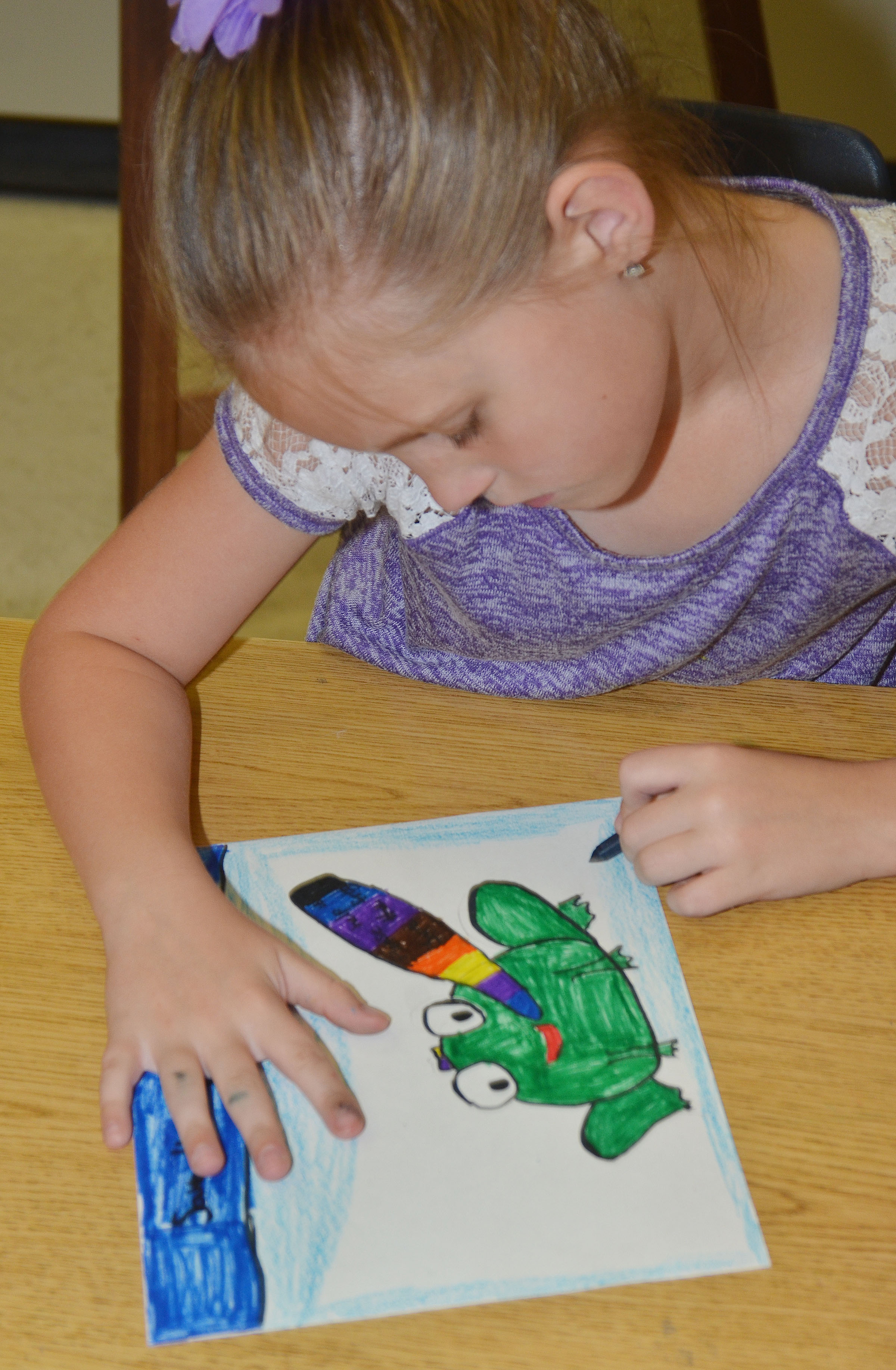 CES third-grader Madisyn Bradfield colors her Save the Frogs artwork.