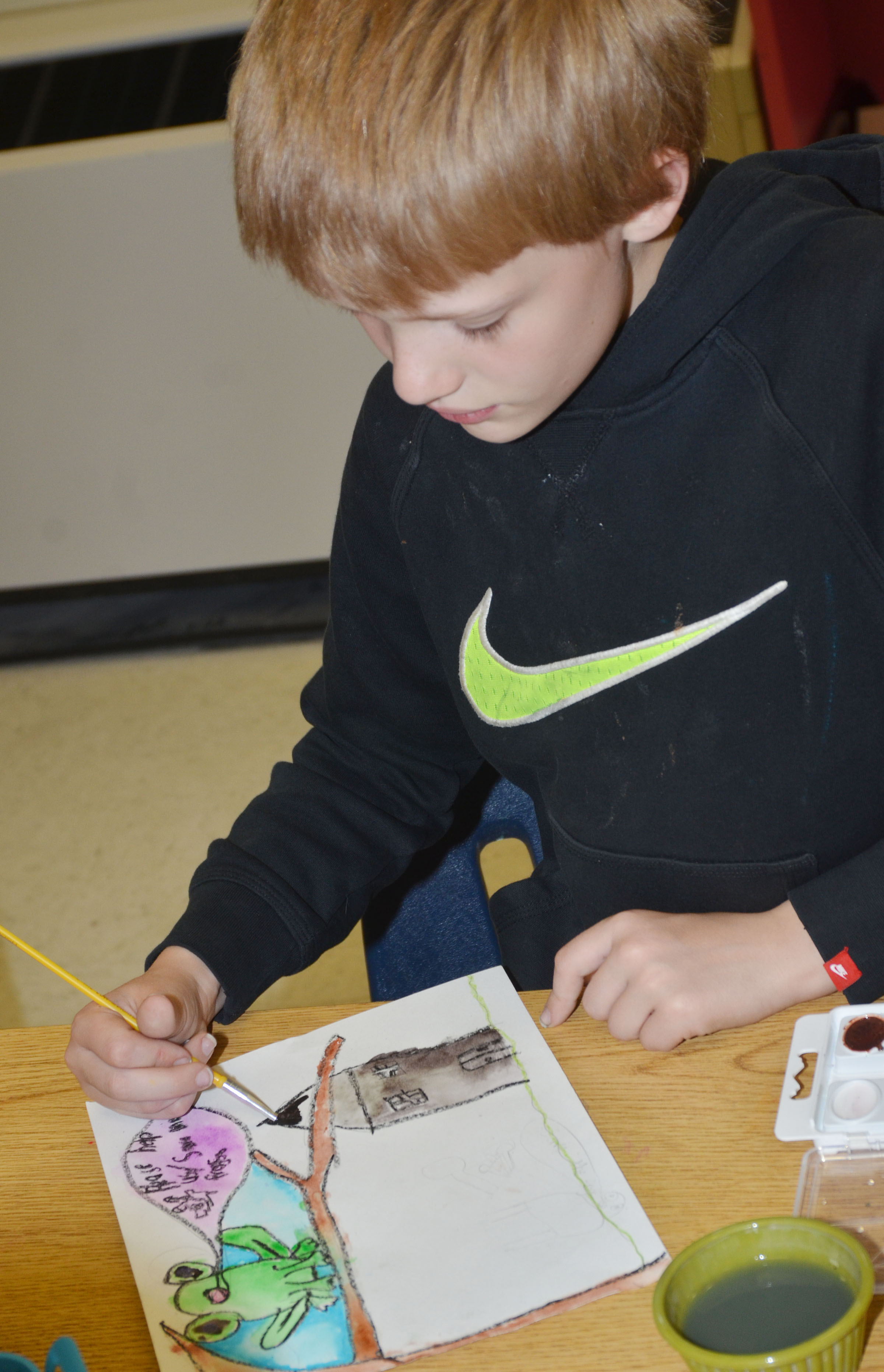 CES third-grader Jonathan Releford paints his Save the Frogs artwork.