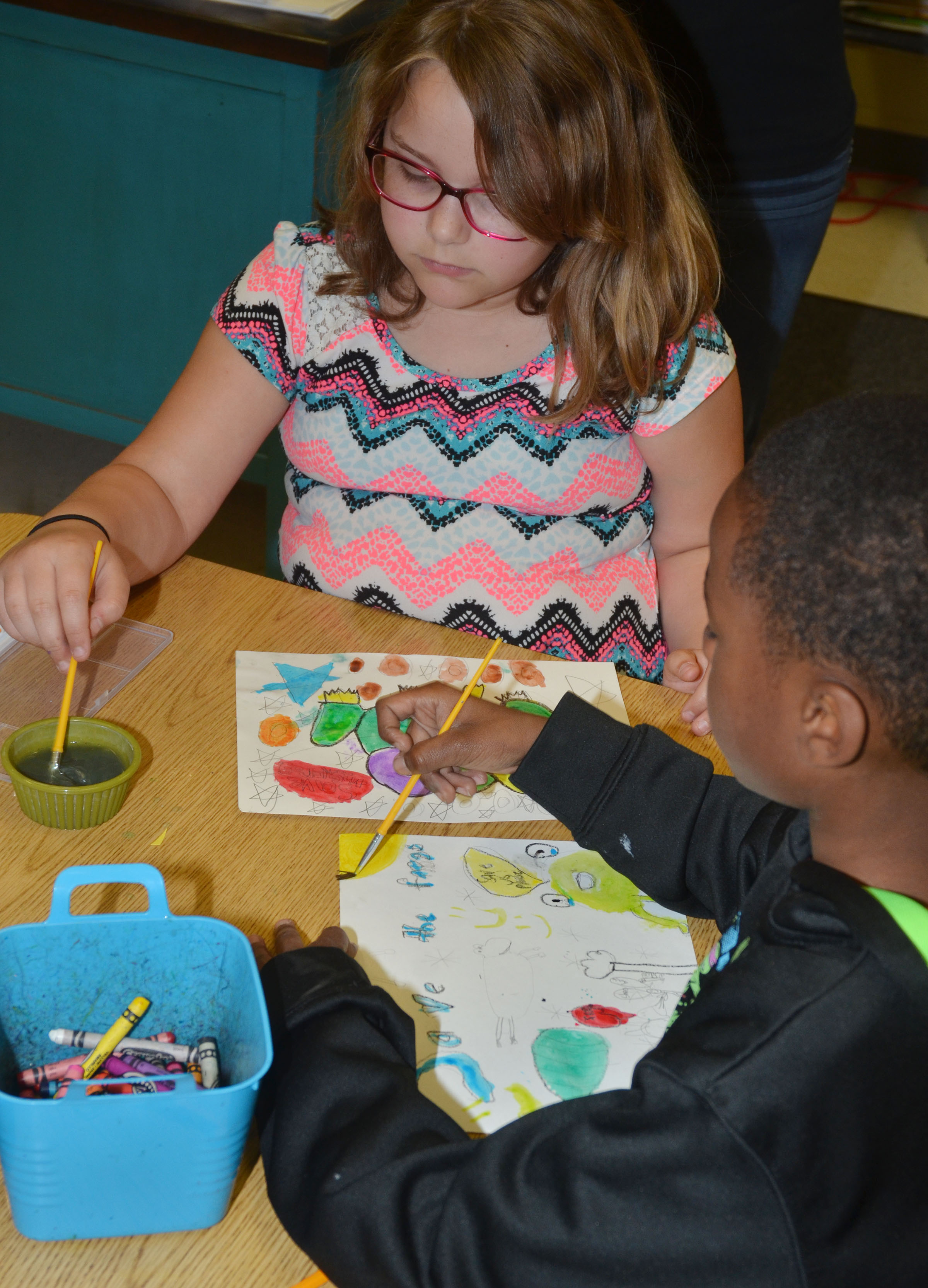 CES third-graders Eleana Brewer, at left, and John Gholston paint their Save the Frogs artwork.