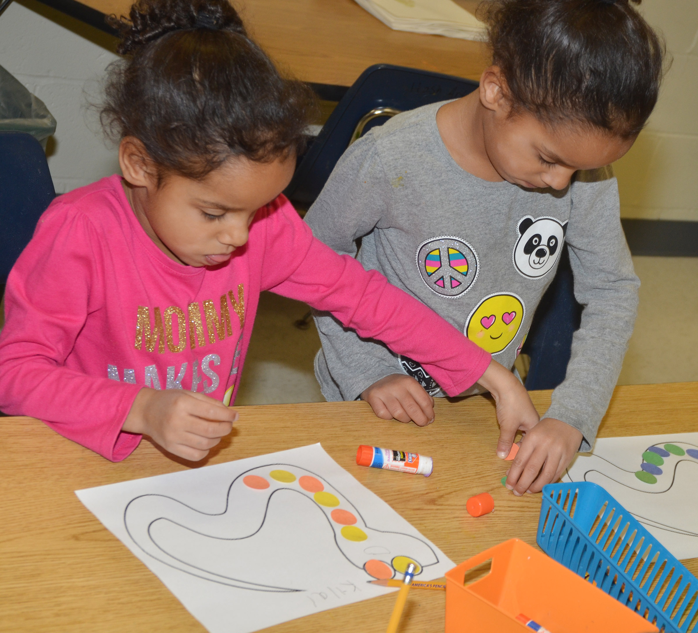 CES kindergarteners Kylei Thompson, at left, and Kaylee Thompson make color patterns on their snakes.