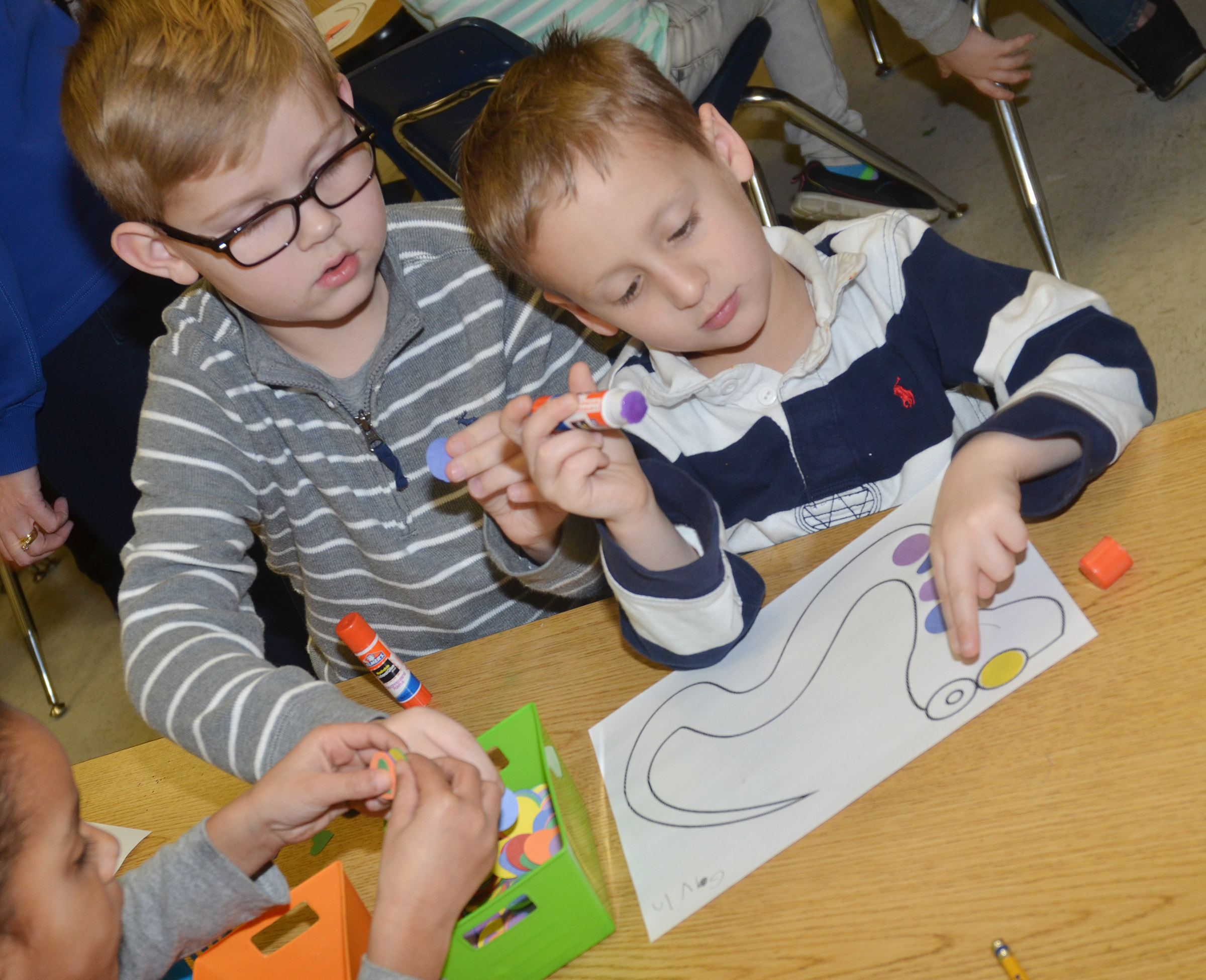 CES kindergarteners John Hagan Newton, at left, and Gavin Paris make color patterns on their snakes.