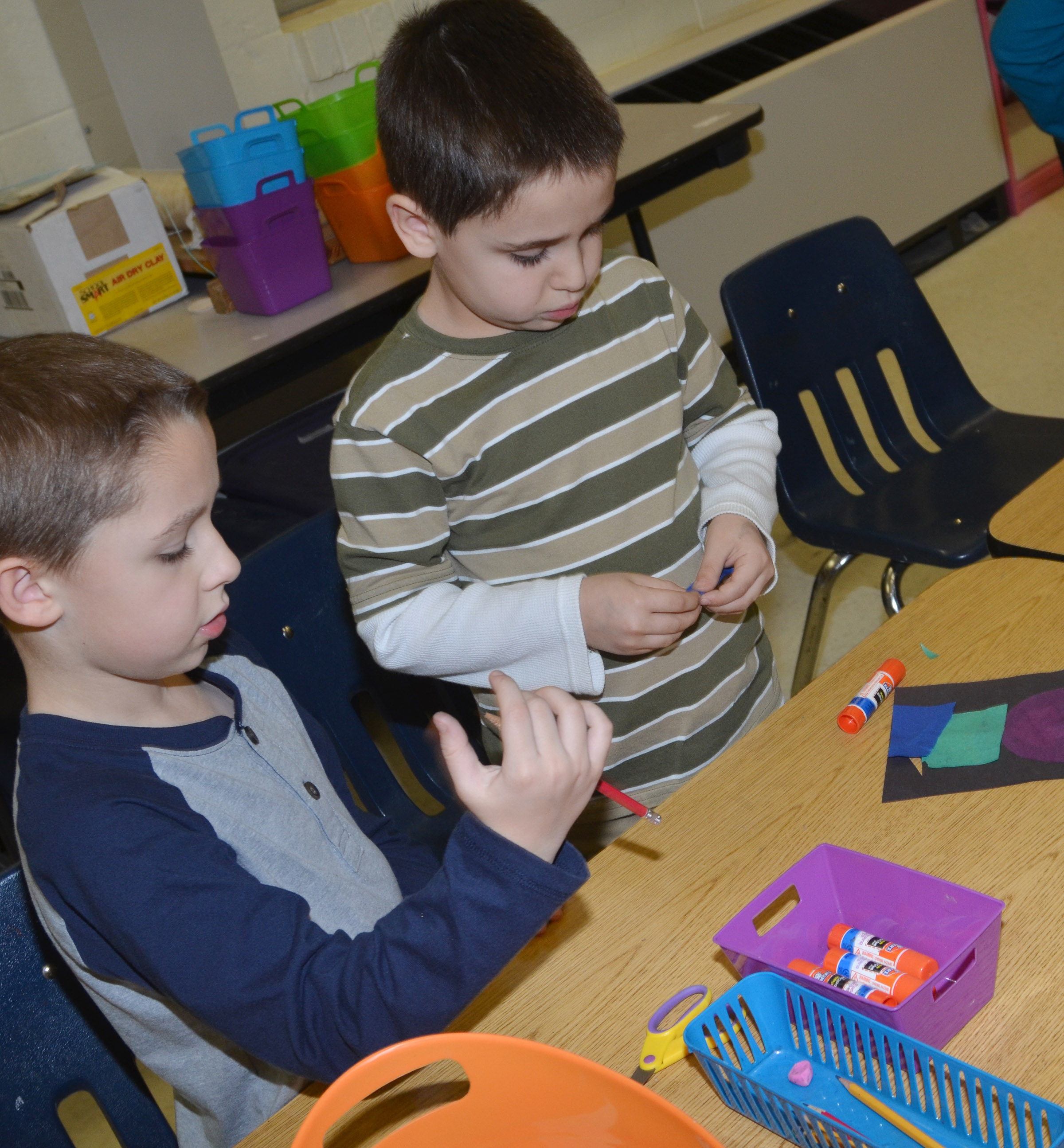 CES first-graders Aiden Forrest, at left, and Aaron Floyd glue their stained glass windows.