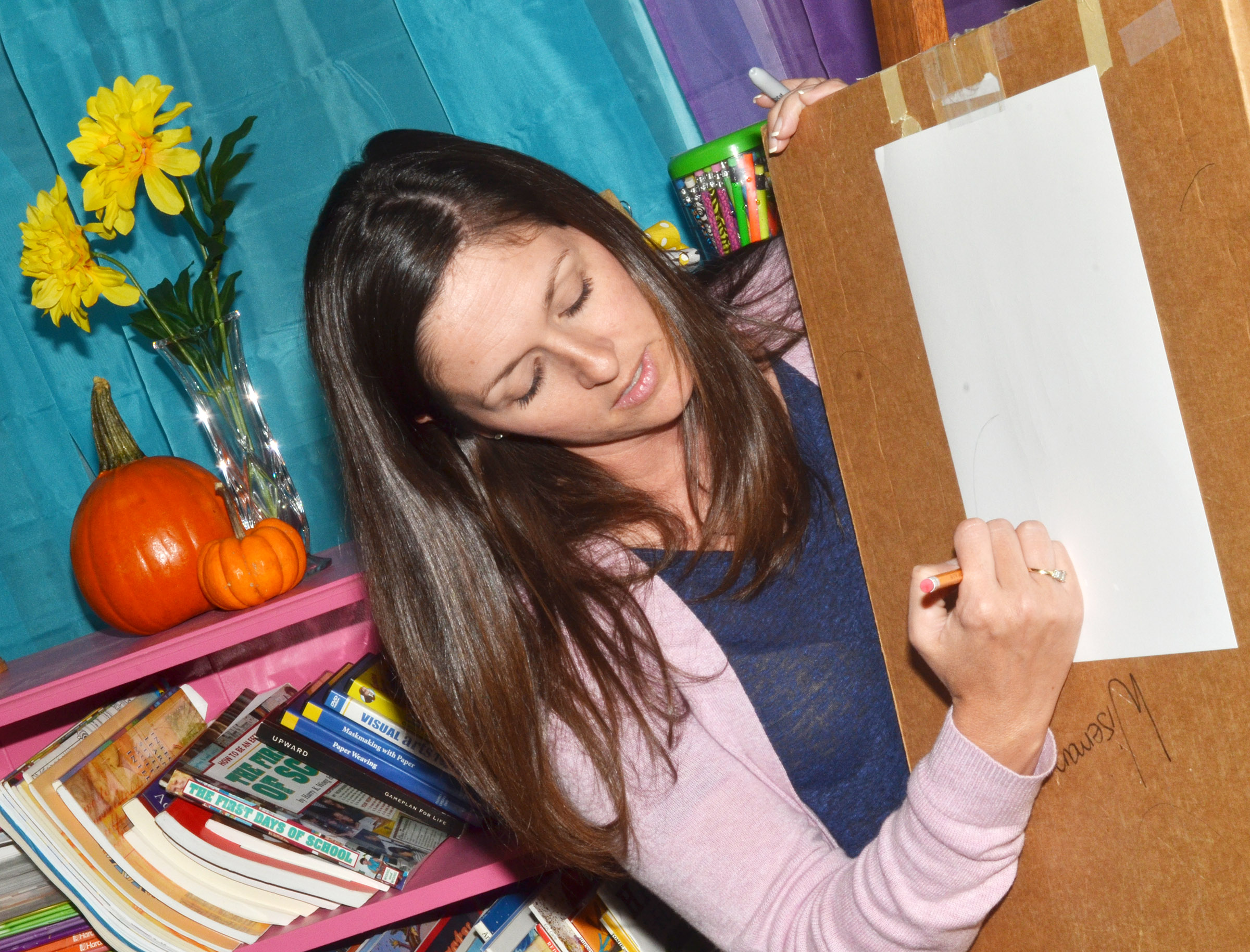 CES art teacher Adrienne Hash shows her students how to draw a still life.