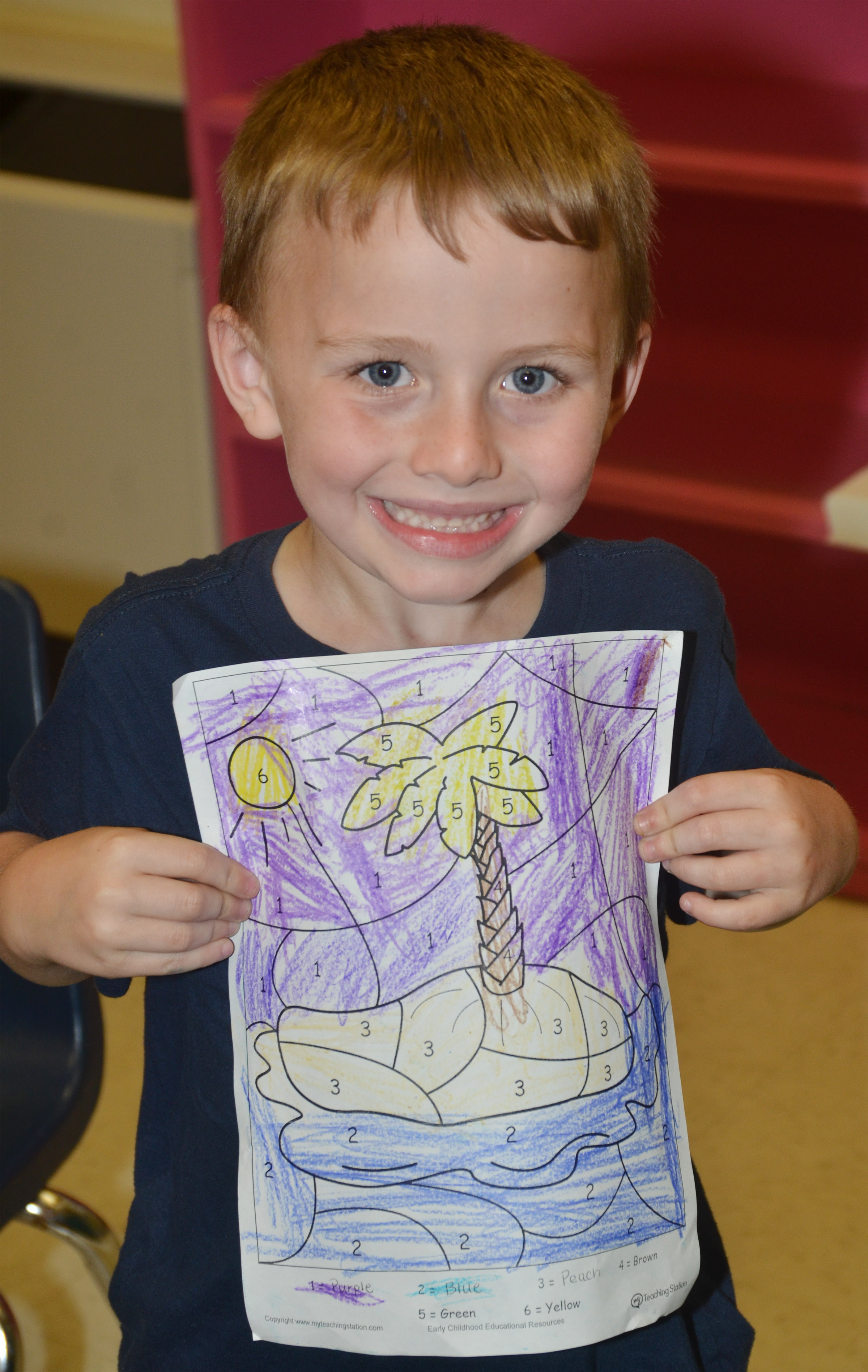 CES kindergartener Ronnie Allen holds his beach drawing.