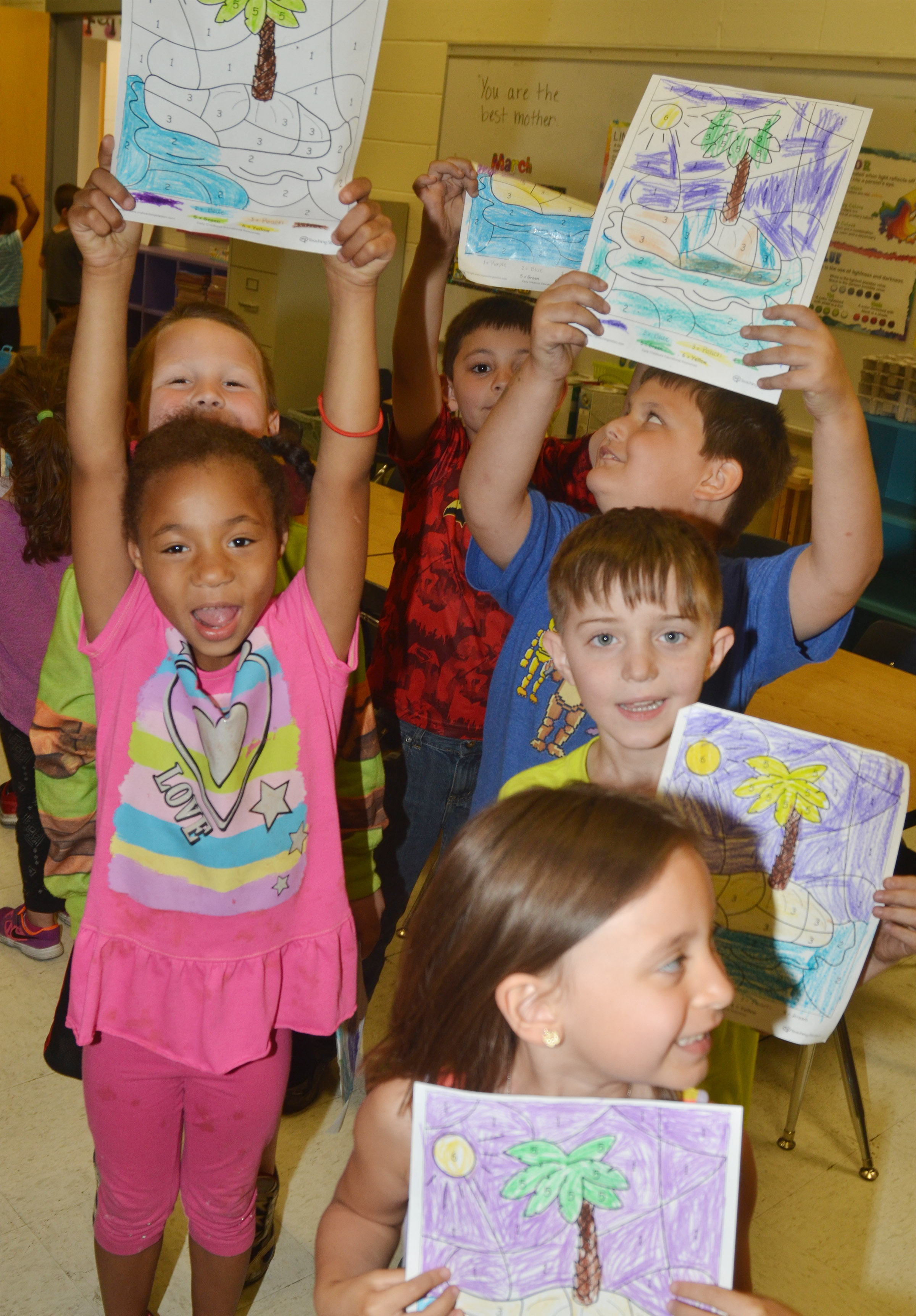 CES kindergarteners hold their beach drawings. In front is Gabrielle Tate. Second row, Brea Miller and Caleb Goodson. Back, Justice Nelson, Keagan Shearer and Cloud Malone.