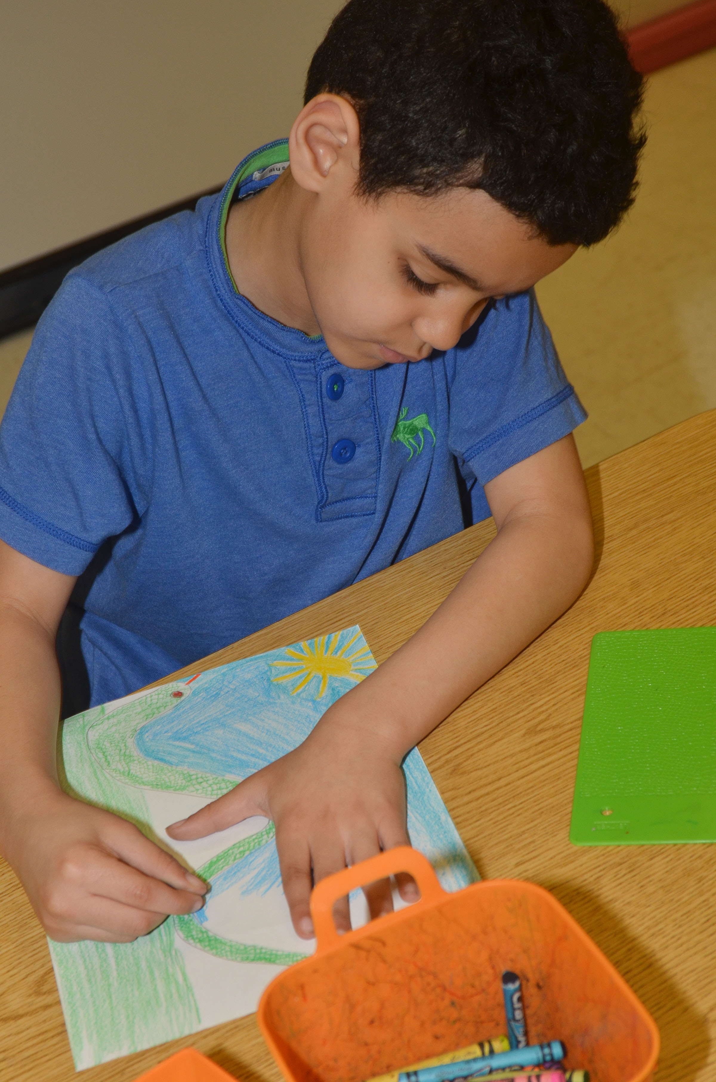 CES second-grader Leshawn Hamilton colors his snake drawing.