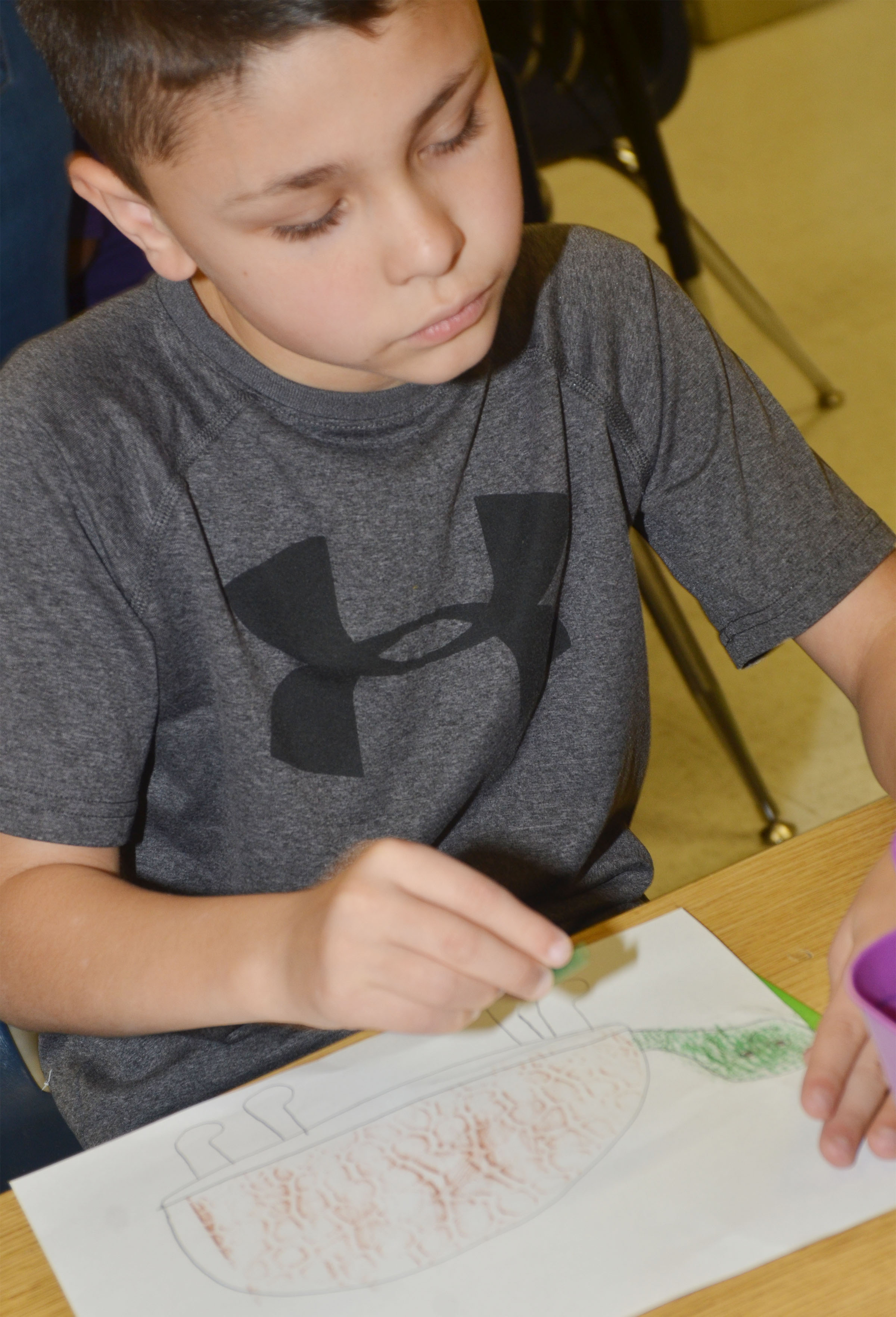 CES second-grader Braygon Noegel colors his turtle drawing.
