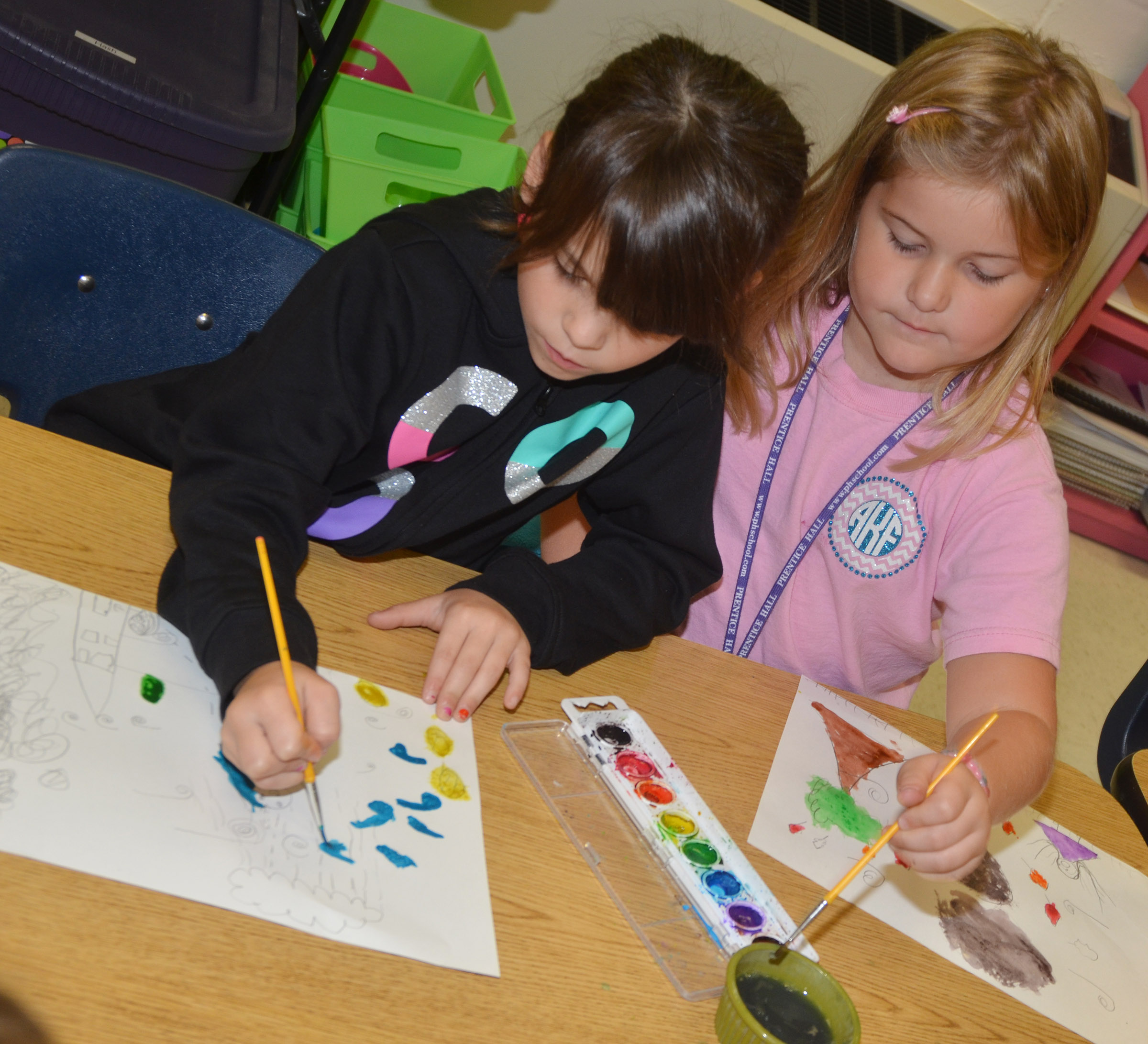 CES first-grader Phoebe Ritchie, at left, and Aubreigh Knifley paint.